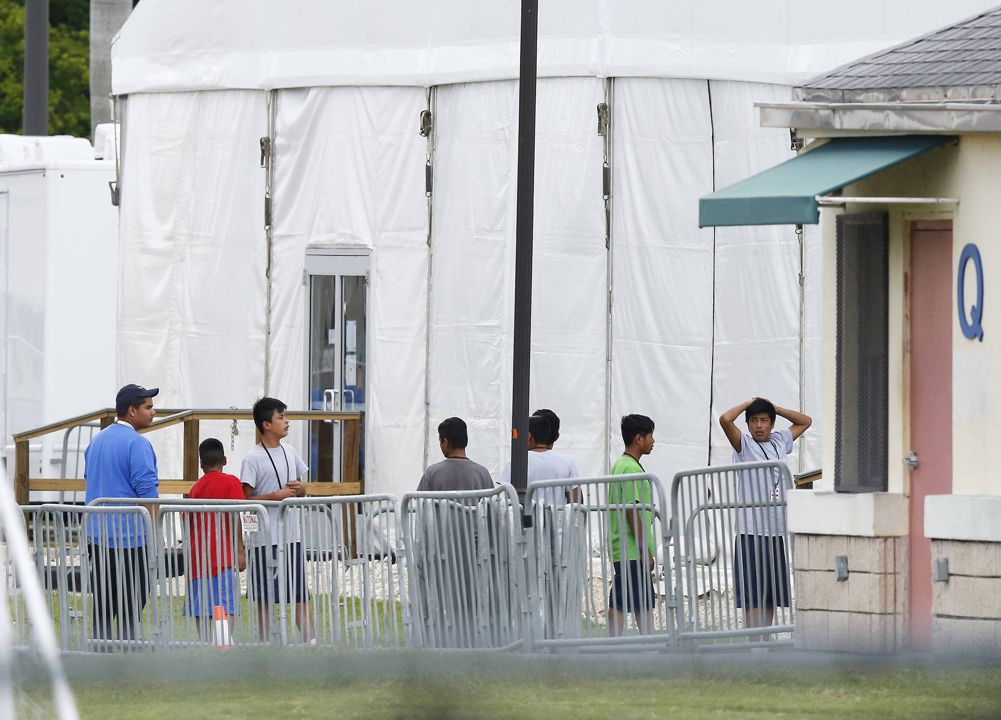 """Immigrant children walk in a line outside the Homestead Temporary Shelter for Unaccompanied Children, a former Job Corps site that now houses them, on Wednesday, June 20, 2018, in Homestead, Florida. U.S. Rep. Carlos Curbelo said he found it """"troubling"""" to see two of his Democratic colleagues turned away from the Miami-area detention center for migrant children. (Brynn Anderson 