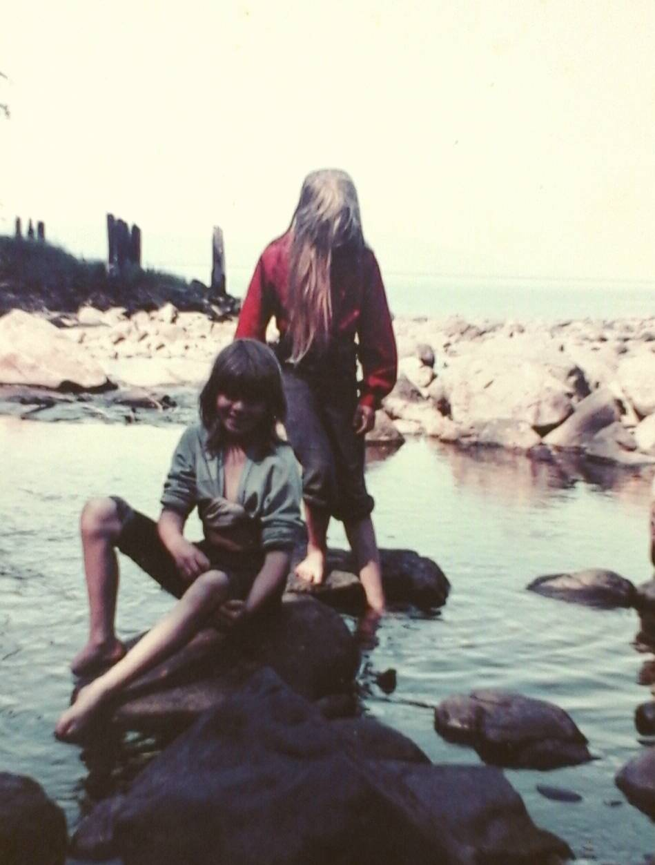 Megan Neilson (front) and author Tara Neilson playing in the cannery creek with the burned pilings in the background.