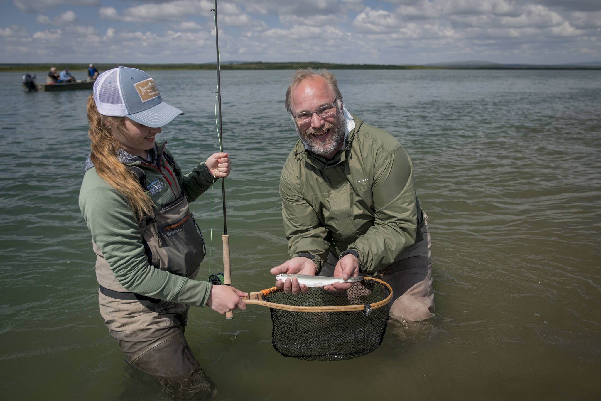 Abbey Whitcomb and her client, Naknek resident Bryon Singly, pose with a small rainbow on the Naknek River. (Courtesy Photo | Sarah Miller)