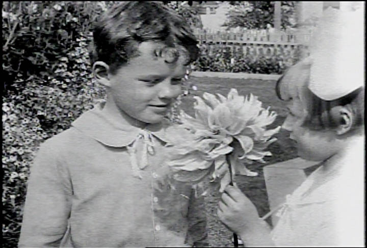 "A still from ""A Day in Skagway,"" the Burton Holmes travelogue produced for Paramount Pictures in 1918. This scene is of a boy and girl (Kenneth Blanchard and Evelyn Curtin) sharing a large dahlia in one of Skagway's beautiful gardens. Photo courtesy of Human Studies Film Archives, Smithsonian Institution; the American Film Institute and the National Film and Sound Archives, Australia."