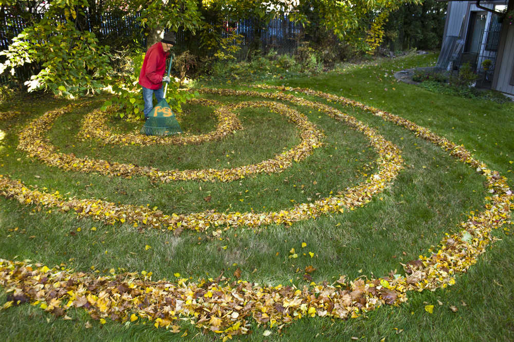 Juneau artist Jay Crondahl adds a little ephemeral art to the lawn at the Park Shore Condominiums on Monday.
