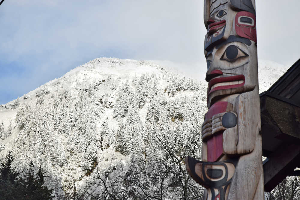 One of two totem poles in front of the Gajaa Hit building in the Willoughby District is seen in front of a snow-covered Mount Juneau on Wednesday, Nov. 11, 2015. A trace of snow was recorded overnight at Juneau International Airport, 0.4 inches in the Mendenhall Valley and 3.6 inches at the base of Eaglecrest Ski Area, but no snow was recorded in downtown Juneau. Alaska's capital city has yet to record measurable snow at the airport, its official measuring site.