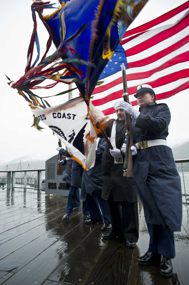 An honor guard made up of U.S. Coast Guard and Navy personnel struggle to hold their flags during wind gusts during a service at the U.S.S. Juneau Memorial downtown on Friday.
