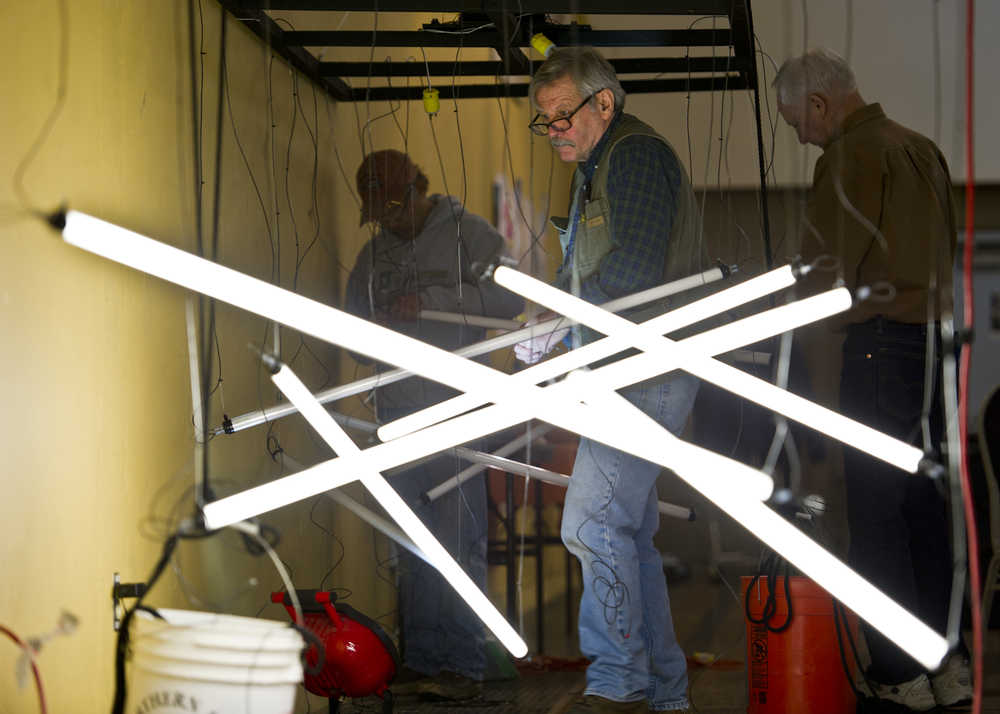 Steve Davis, center, volunteers with Bing Carrillo, left, and Joe Carlson on Thursday at the Juneau Arts & Culture Center to build creative lighting for the Wearable Art Extravaganza to be held Saturday and Sunday, Feb. 13-14. Saturday's show is sold out and as of Thursday 130 tickets remain for Sunday's show. According to Nancy DeCherney, executive director for the Juneau Arts and Humanities Council, volunteers are still needed.