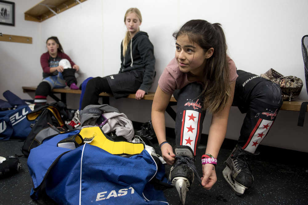 Kaylee Lahnum, 13, laces up her ice skates before the Juneau Douglas Ice Association 10U girls hockey game against the 10U boys team on Dec. 17, 2016 at the Treadwell Arena. The 10U boys team won 7-5.