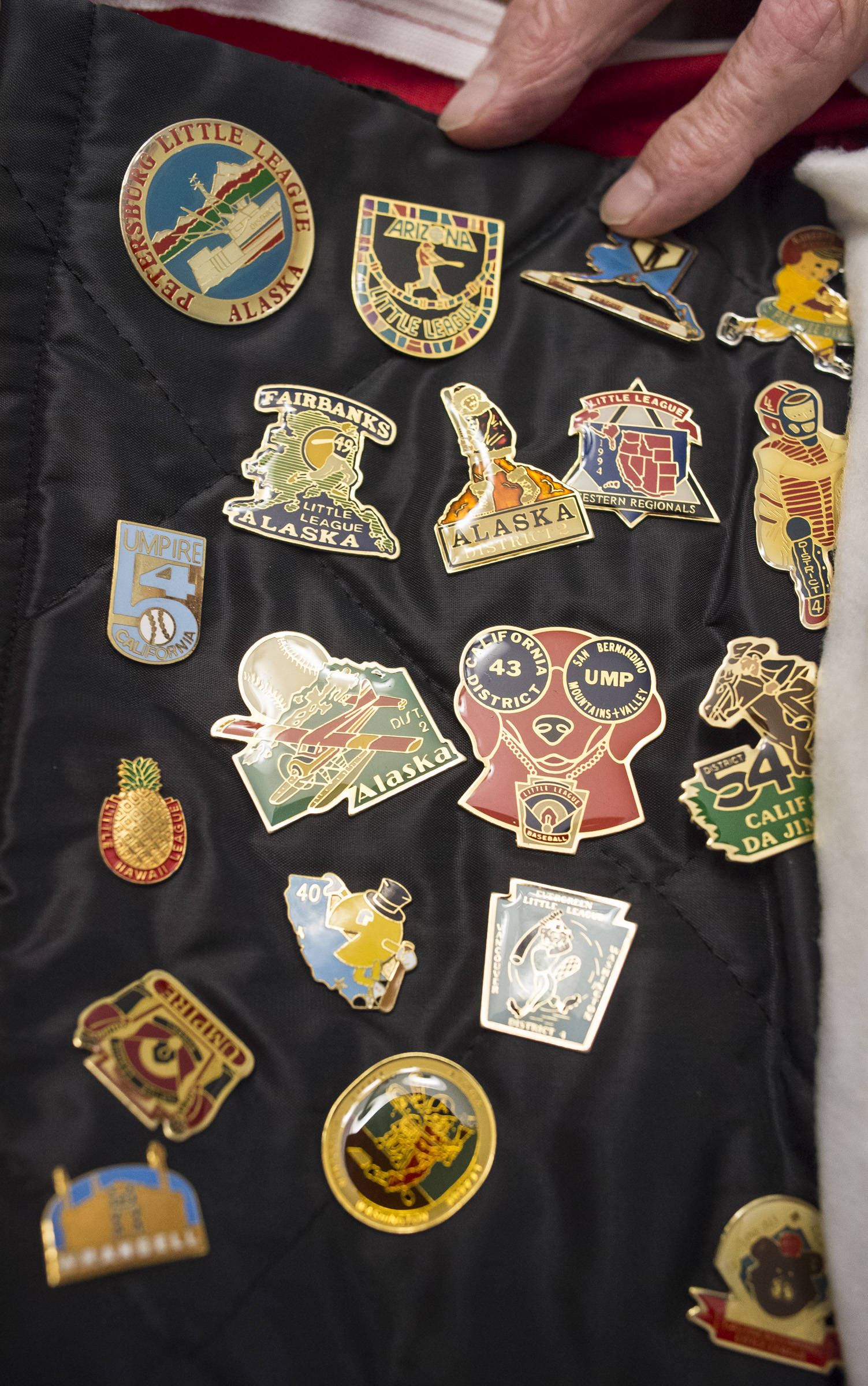 Tom Karpstein, 70, show a portion of his collection of baseball tournament pins as he talks Thursday, August 2, 2018, about his long baseball umpiring role in Juneau. (Michael Penn | Juneau Empire)