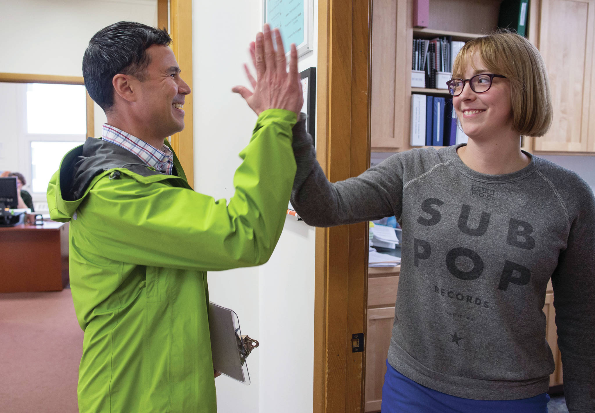 Norton Gregory gives Carole Triem a high-five as he arrives at City Hall to resign from his Assembly seat to run for mayor on Monday, August 13, 2018. Triem was waiting for Gregory to resign so she could file to run for his areawide seat. The Candidate Filing Period for the Oct. 2 Municipal Election closed Monday. (Michael Penn | Juneau Empire)