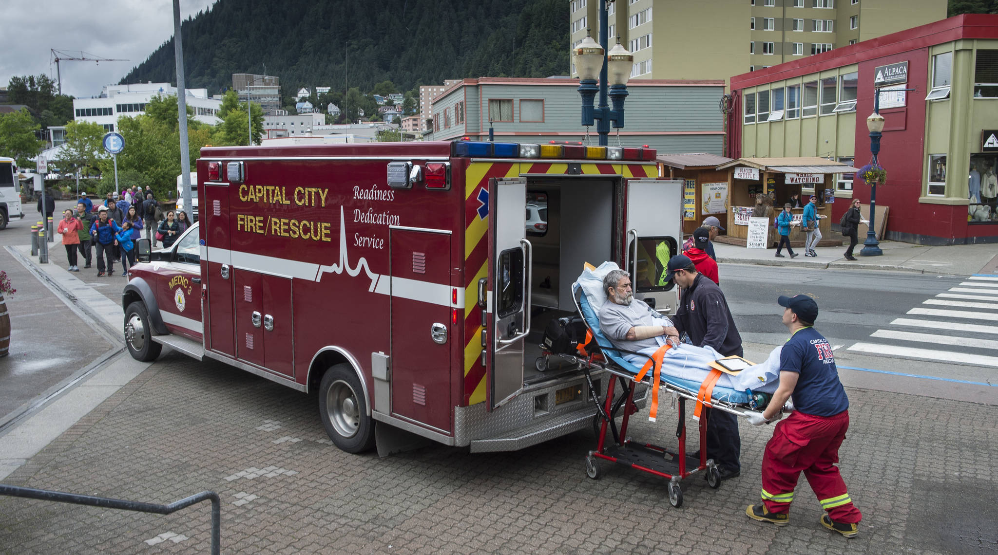 A Capital City Fire/Rescue crew transports a cruise ship passenger off the Radiences of the Seas downtown on Tuesday, August 14, 2018. (Michael Penn | Juneau Empire)