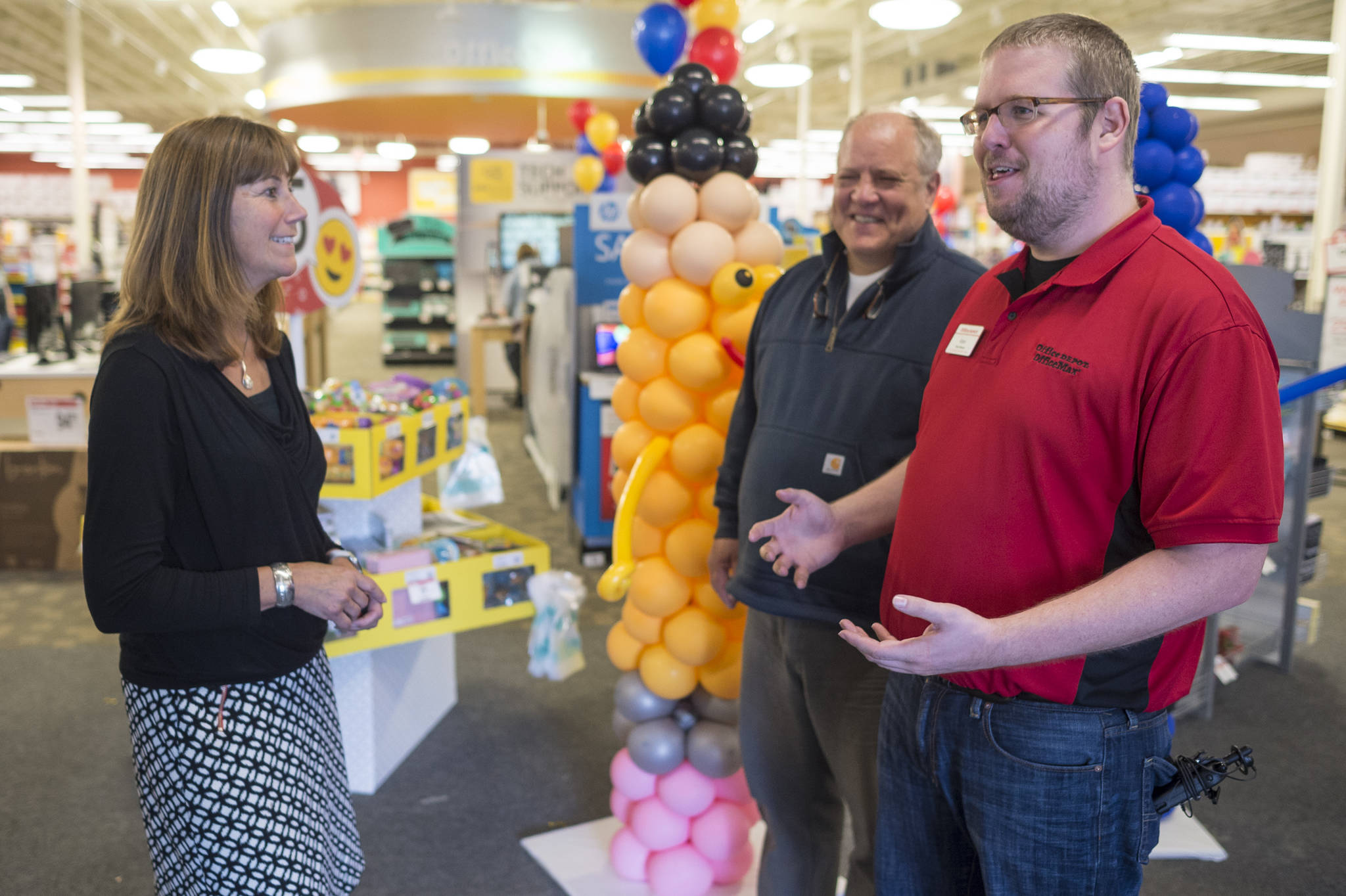 Dr. Bridget Weiss, Interim Juneau School District Superintendent, left, and Harborview Elementary School special education teacher Steve Byers, center, speak with Office Max store manager Adam Dordea on Thursday, August 16, 2018, during a store fundraising event for elemenary schools. Office Max pledged to donate up to $10,000. (Michael Penn | Juneau Empire)