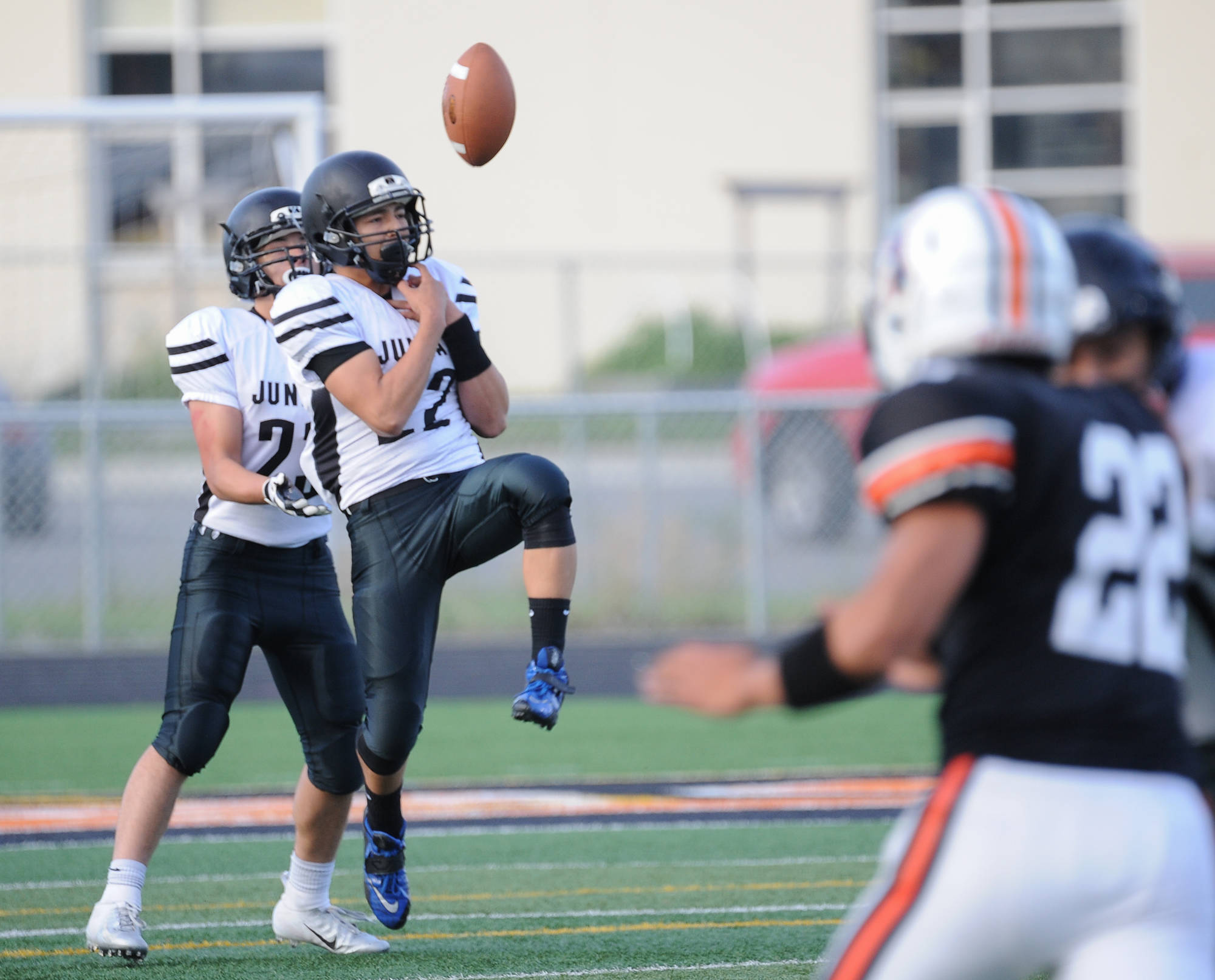 Juneau's Ali Beya has difficulty handling a kickoff in front of teammate Cody Morehouse. (Michael Dinneen | For the Juneau Empire)