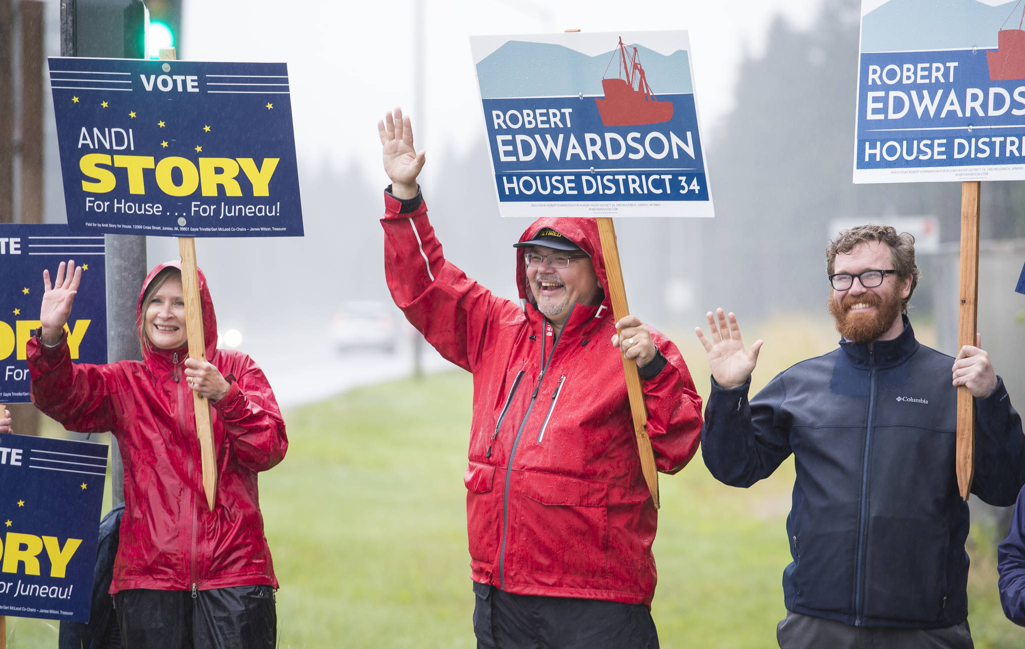 House District 34 candidates Andi Story, left, and Rob Edwardson, center, wave campaign signs with Rep. Justin Parish, D-Juneau, at Egan Drive and Glacier Highway on Tuesday, Aug. 21, 2018. (Michael Penn | Juneau Empire)