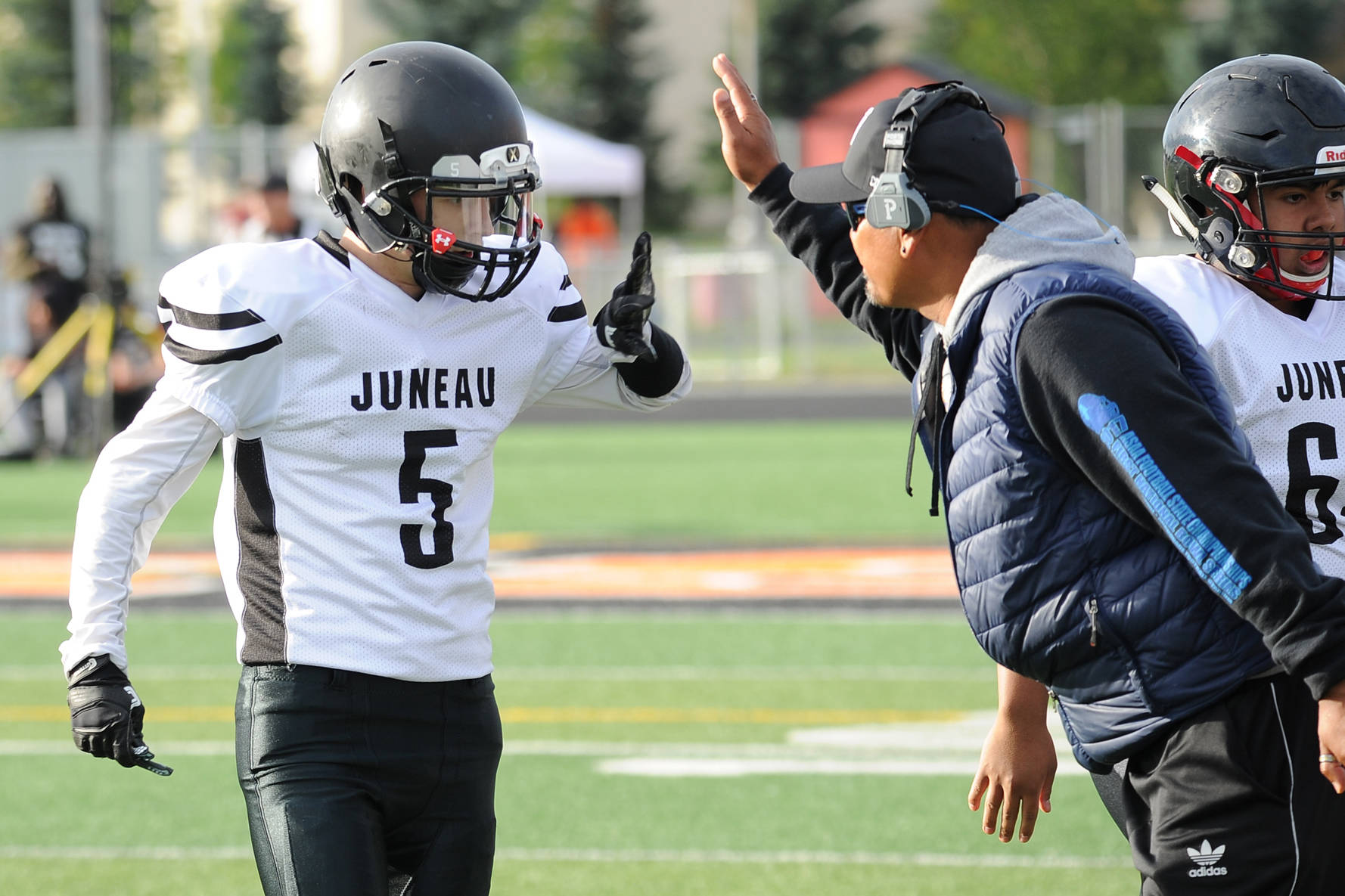 Hansel Hinckle is congratulated by coach Randy Quinto following his interception return for a touchdown last Saturday. (Michael Dineen | For the Juneau Empire)