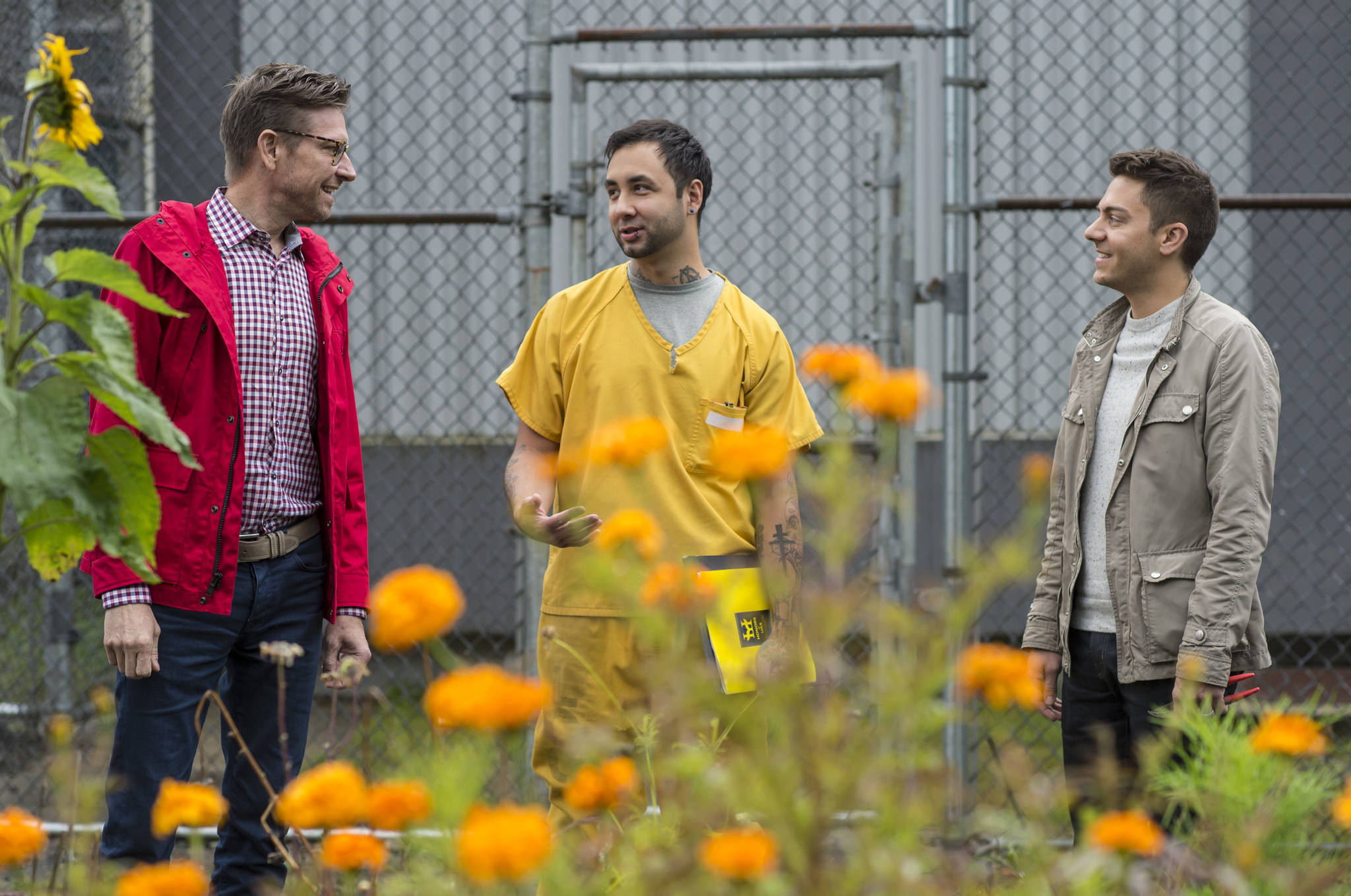 Jeremy Bauer, left, and Jason Clifton, right, of Frenchie's Floral Studio, talk with inmate Patrick Sweeney about a flower-growing collaboration at Lemon Creek Correctional Center on Friday, Aug. 24, 2018. (Michael Penn | Juneau Empire)