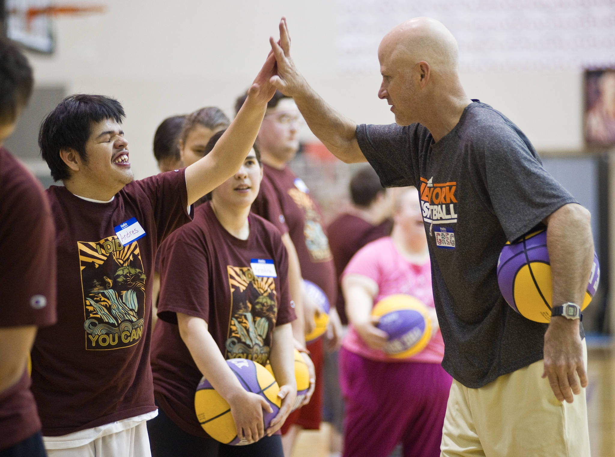 Greg Brittenham gives Andres Jones a high five during a three-day basketball camp for physically and mentally challenged athletes at Juneau-Douglas High School in June of 2014. (Michael Penn | Juneau Empire File)