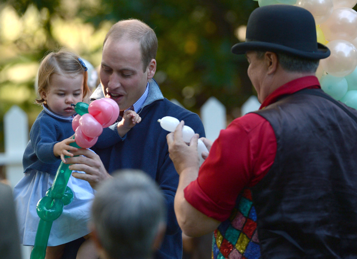 Britain's Prince William, the Duke of Cambridge, holds Princess Charlotte, as she is given a balloon animal during a children's tea party at Government House in Victoria, British Columbia, Thursday