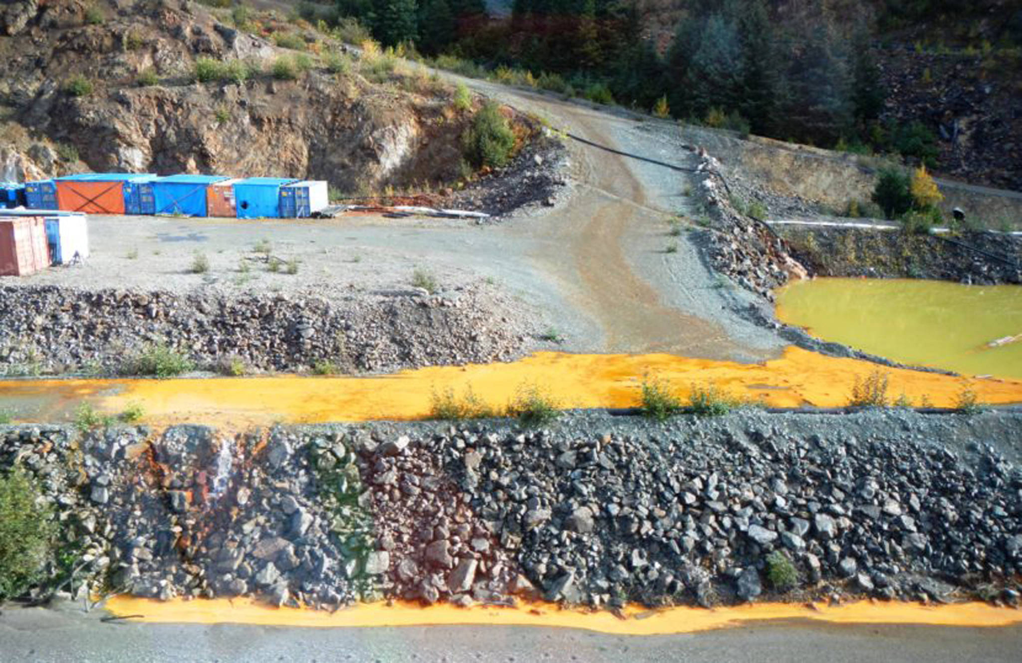 """The Tulsequah Chief Mine is seen on Sept. 26, 2016. The yellow water is Acidic Mine Drainage from shuttered mine adits. It drains into an """"exfiltration pond,"""" pictured, which overflows into the Tulsequah River. (Courtesy Photo)"""