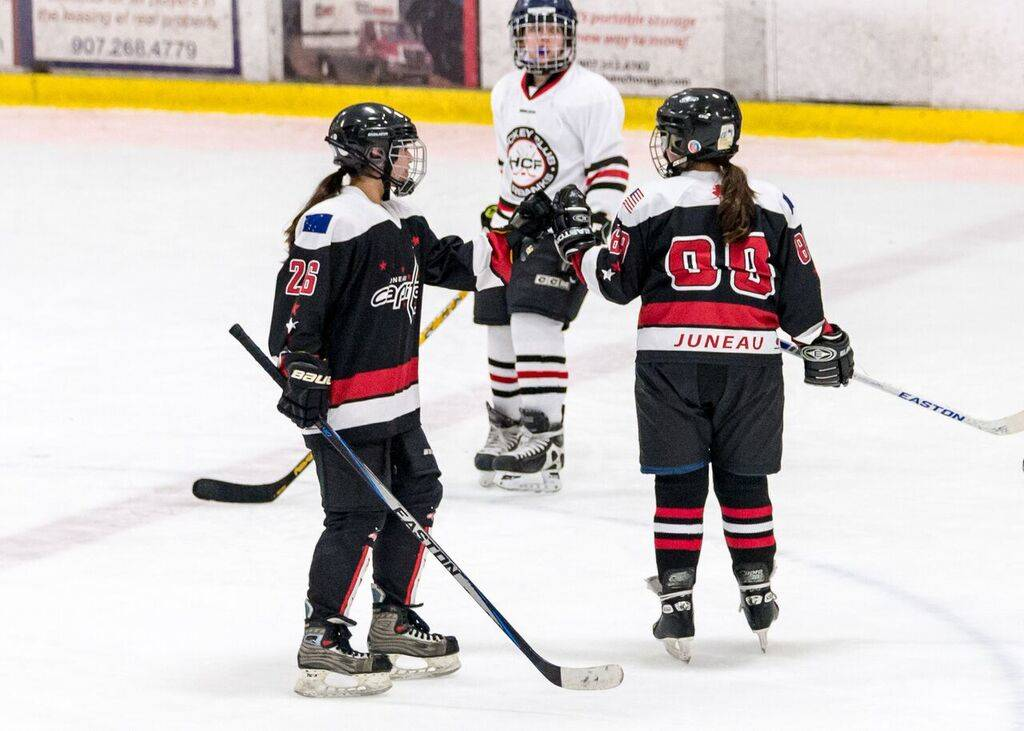 PHOTOS COURTESY OF KIM HORT Nikki Lanhum, left, fist bumps Paige Adams during the Juneau Capitals game against Hockey Club Fairbanks on Friday at the Subway Sports Centre in Anchorage.