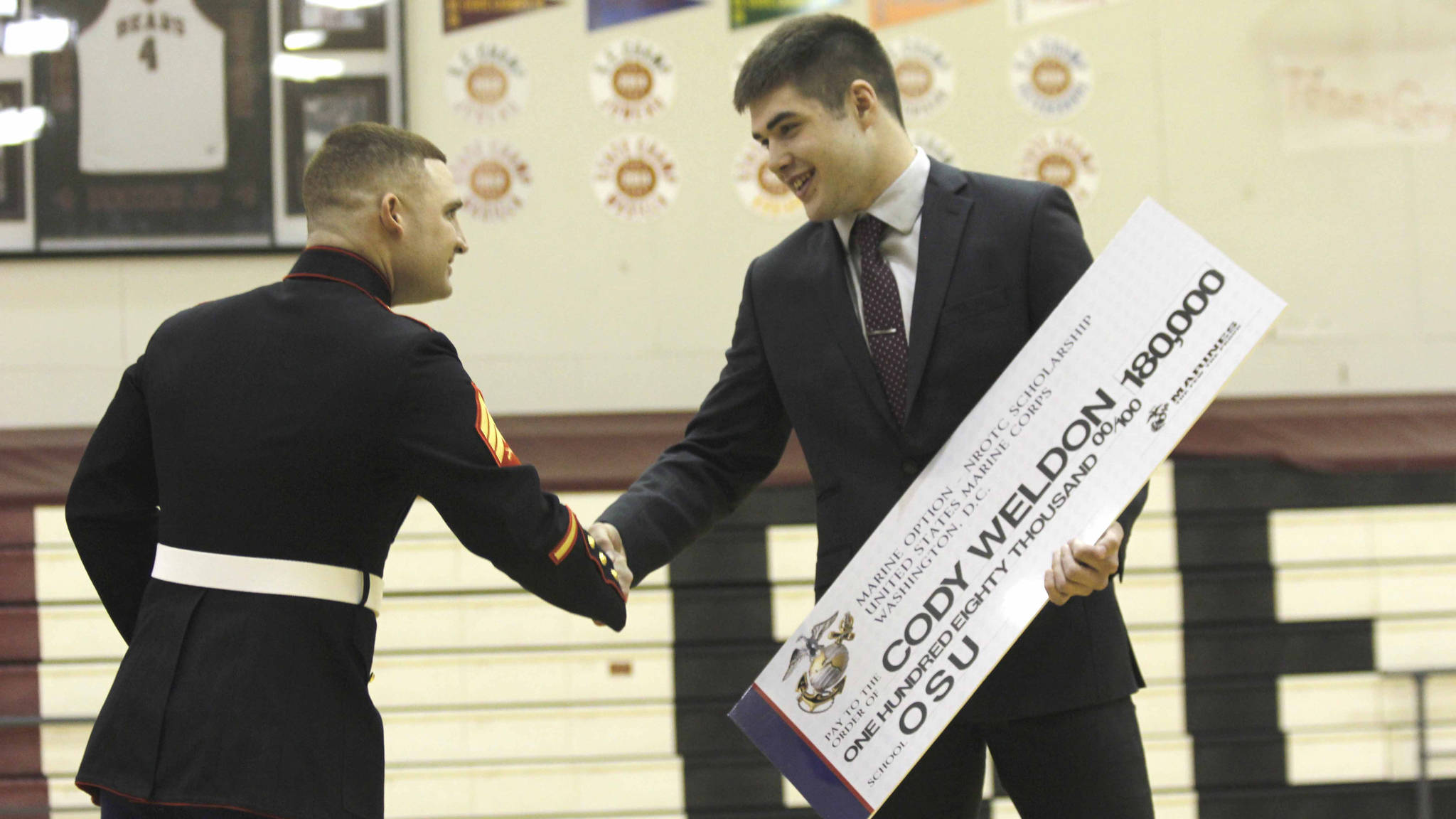 US Marine Sgt. James White congratulates Cody Weldon, 18, with the Naval Reserve Officer Training Corps scholarship Tuesday, April 18, at Juneau-Douglas High School. Weldon was one of two Alaskan high school students to be given the scholarship. (Photo by Alex McCarthy)
