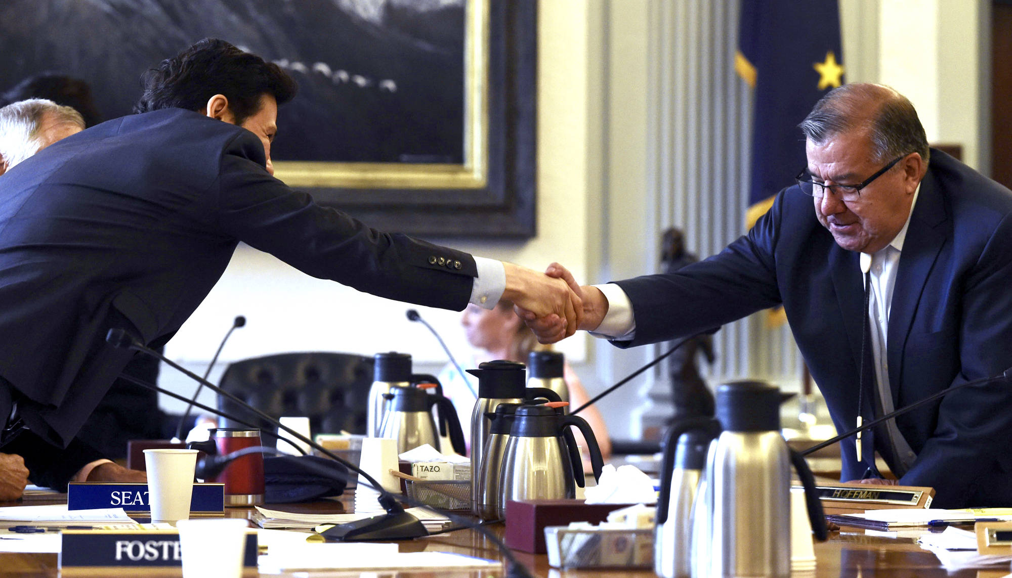 Rep. Neal Foster, D-Nome, left, shakes hands with Sen. Lyman Hoffman, D-Bethel, after an agreement is made on the capital budget in conference committee at the Capitol on Thursday, July 27, 2017. (Michael Penn | Juneau Empire)