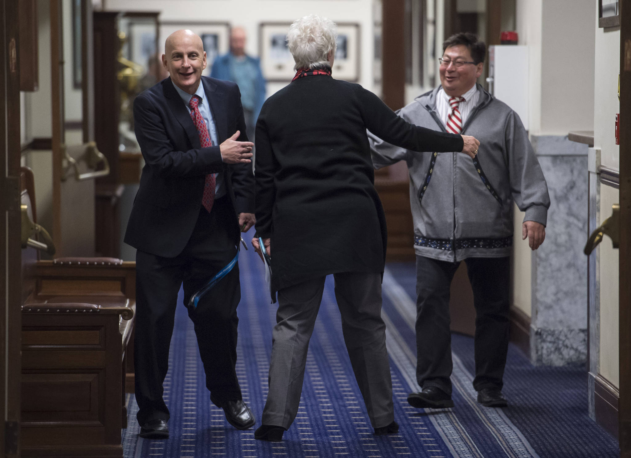 Rep. Daniel Ortiz, NA-Ketchikan, left, Rep. Louise Stutes, R-Kodiak, center, and Rep. Dean Westlake, D-Kotzebue, greet each other on the first day of the fourth Special Session of the 30th Alaska Legisture on Monday, Oct. 23, 2017.