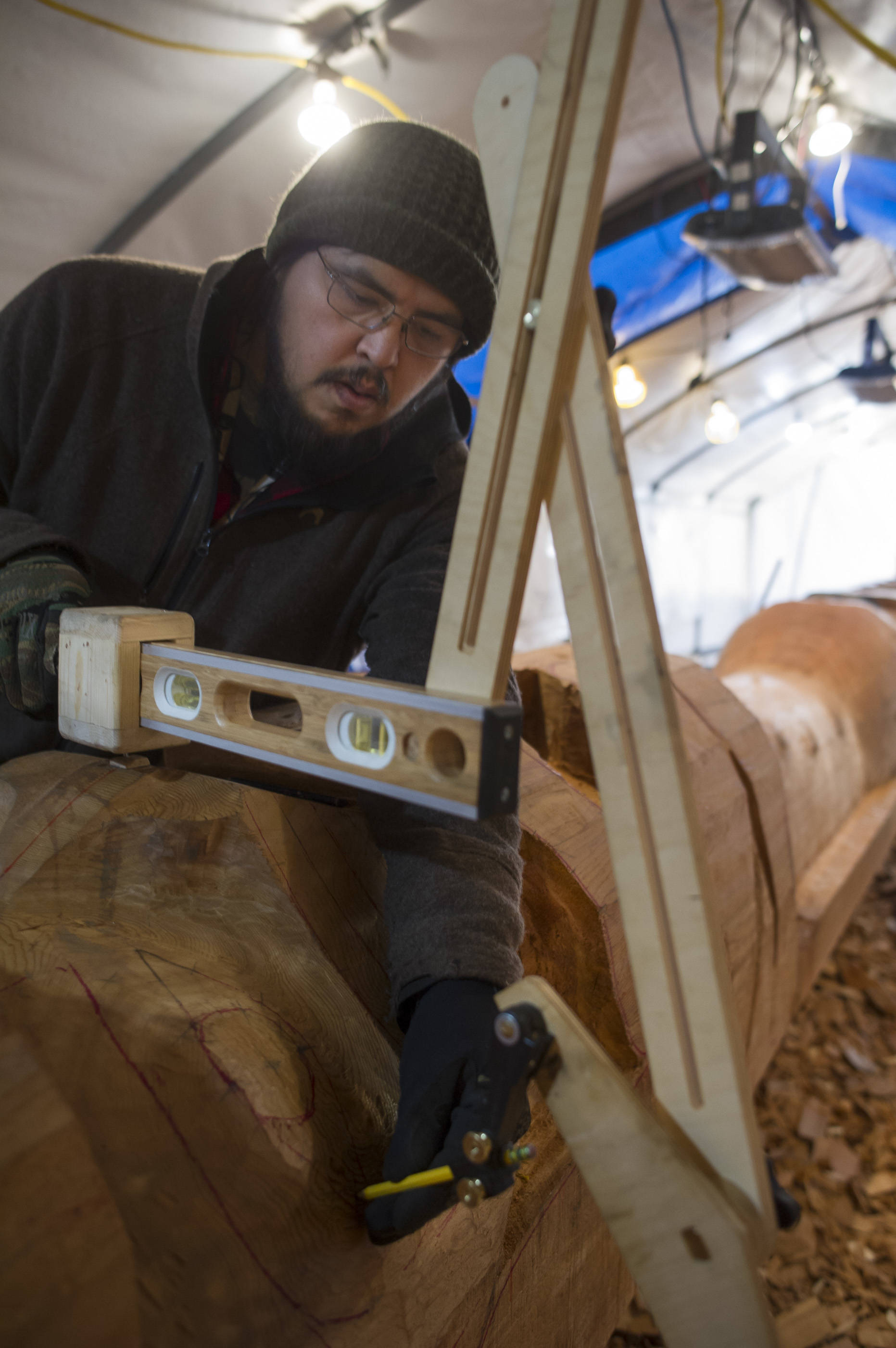 Herb Sheakley works on the Wolf Totem Pole at Harborview Elementary School on Tuesday, Dec. 5, 2017. (Michael Penn | Juneau Empire)