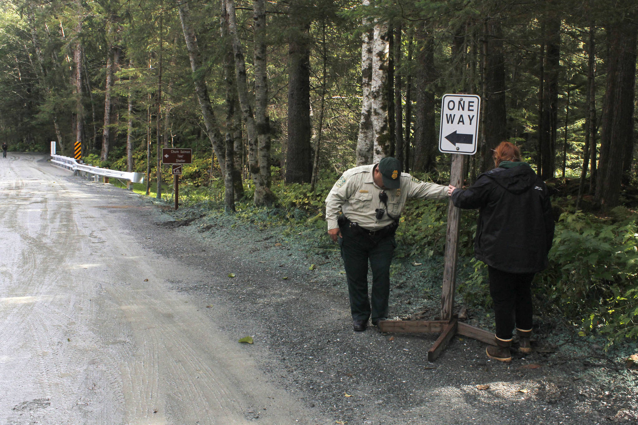 U.S. Forest Service Officer Dave Zuniga and U.S. Forest Service Cabins and Recreation employee Caty Beckel place a road sign at the newly improved Lena Beach Recreation Area on Saturday, Sept. 1, 2018. (Alex McCarthy | Juneau Empire)