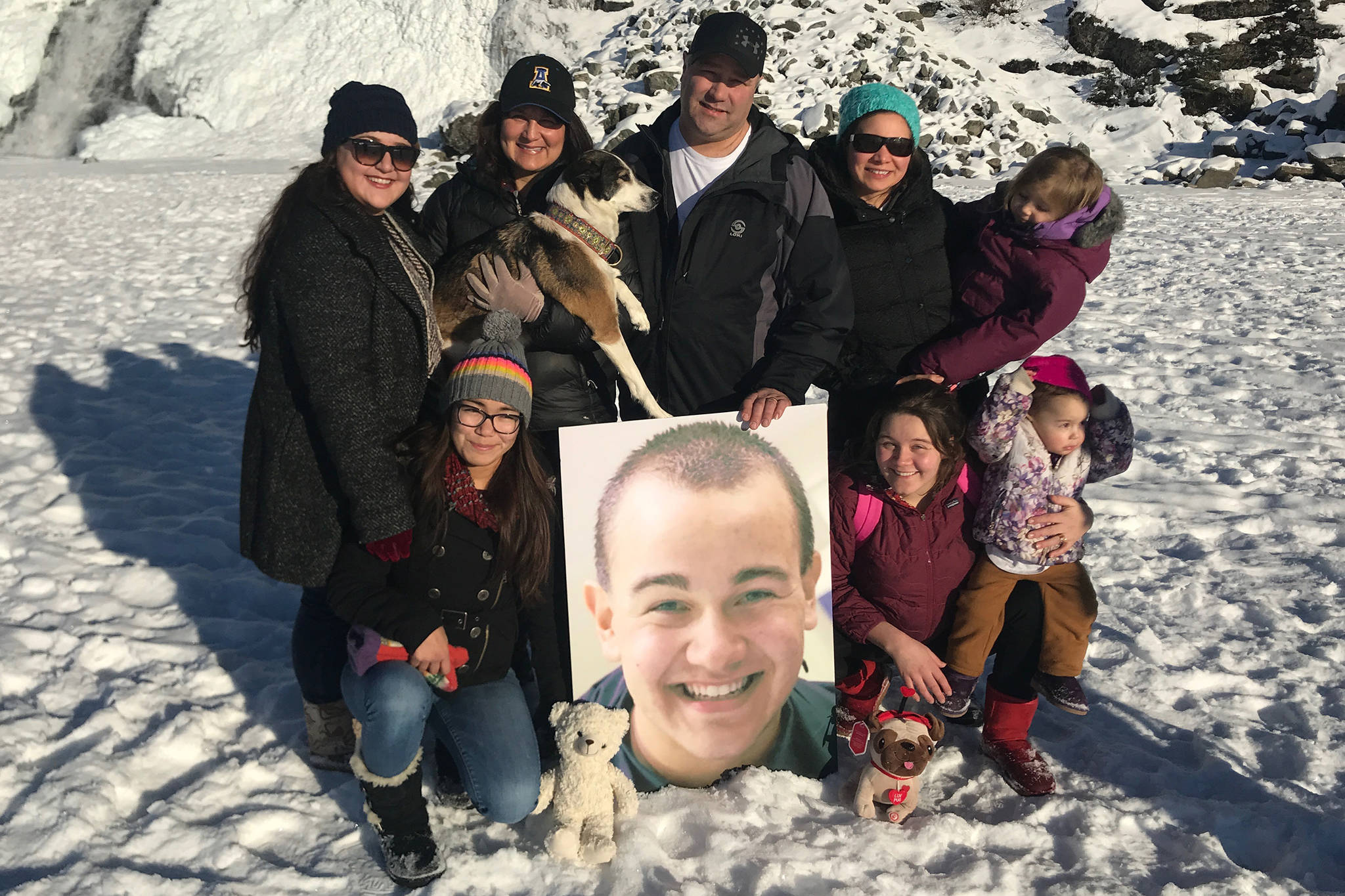 Members of the Eyre family pose at the Mendenhall Glacier with a photograph of Cody Eyre, who was shot and killed by law enforcement on Christmas Eve 2017. (Courtesy Photo | Eyre Family)