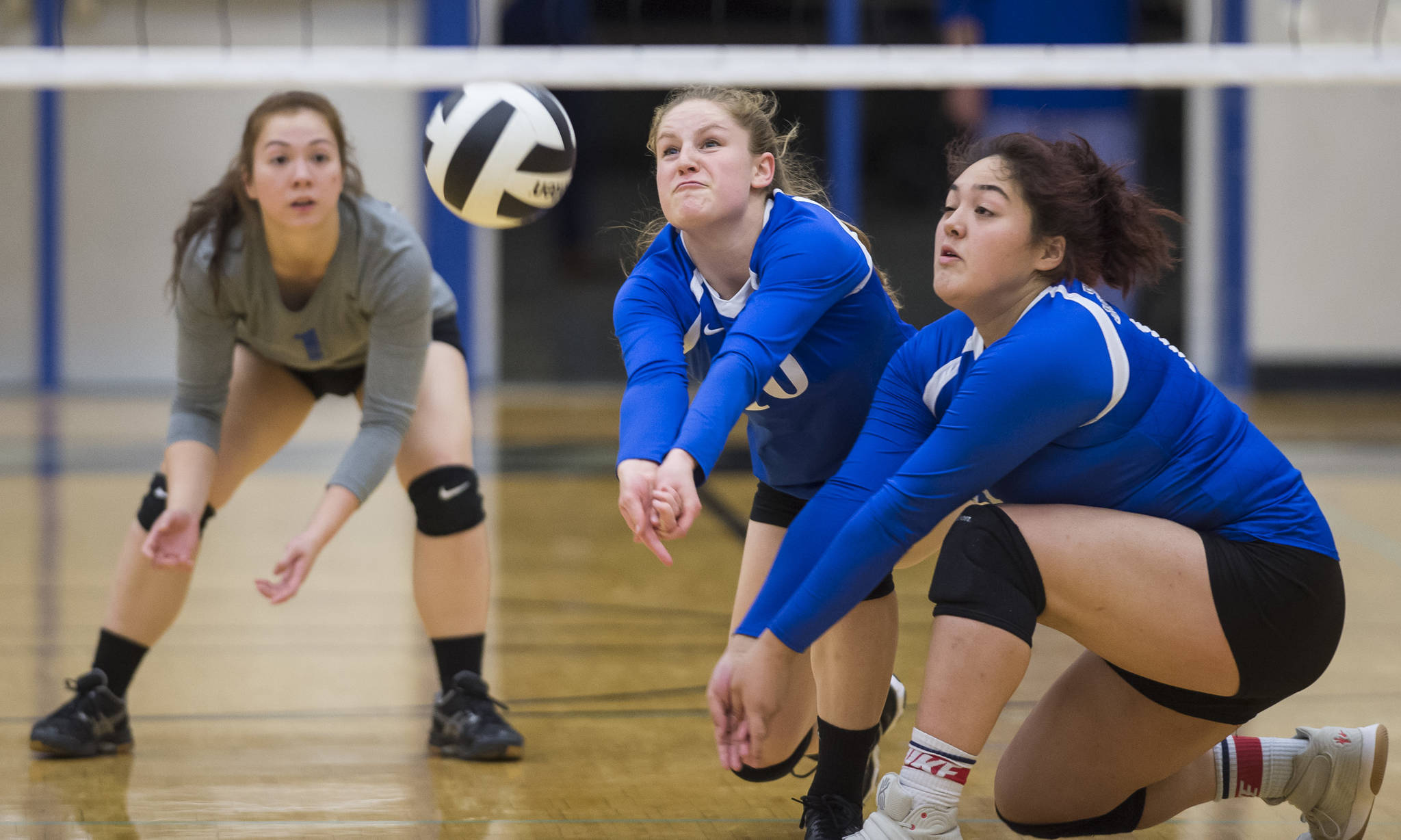 Thunder Mountain's Audrey Welling, center, bumps the ball up against Ketchikan backed up by teammates Tasi Fenumiai, right, and Leilani Eshnaur at TMHS on Friday, Sept. 14, 2018. TMHS won 3-0. (Michael Penn | Juneau Empire)