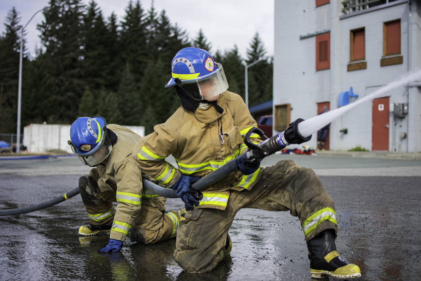 JDHS student Finn Adam (left) and homeschool student James Zuiderduin (right), Capital City Fire/Rescue cadets, practice advancing a hose under pressure at their final day of training with the CCFD on Saturday, April 21, 2018. (Richard McGrail | Juneau Empire File)