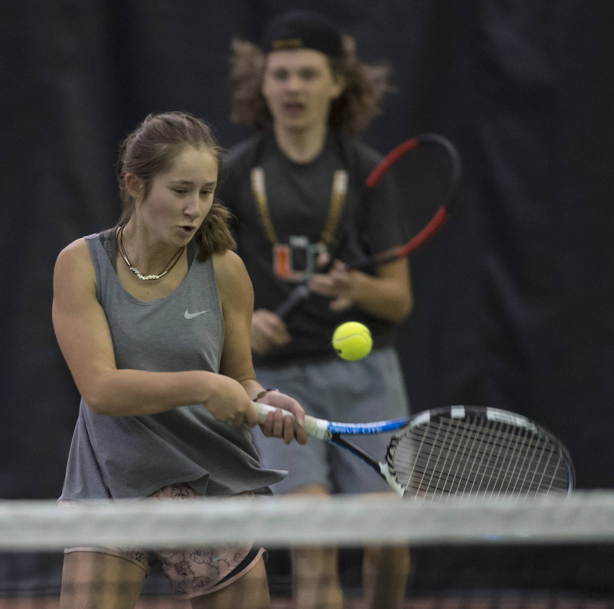 Adelie McMillan volleys a ball against the team of Olivia Moore and River Reyes-Boyles during the Regional Tennis Championships at the JRC/The Alaska Club on Saturday. McMillian is backed up by her partner Wolf Dostal in the mixed doubles match. (Michael Penn | Juneau Empire)