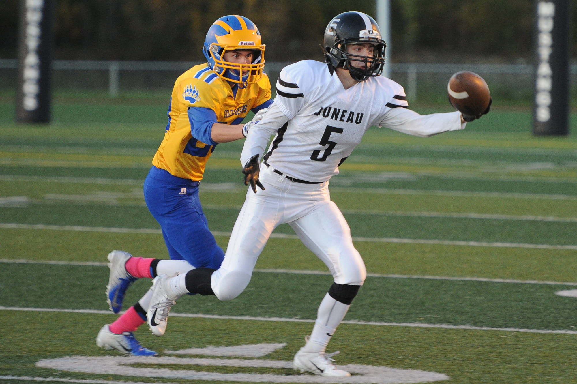 Juneau's Hansel Hinckle reaches for a pass as Bartlett defender Josh Siania closes in at Chugiak High School in Anchorage on Saturday, Sept. 29. Bartlett won 65-12. (Michael Dinneen | For the Juneau Empire)