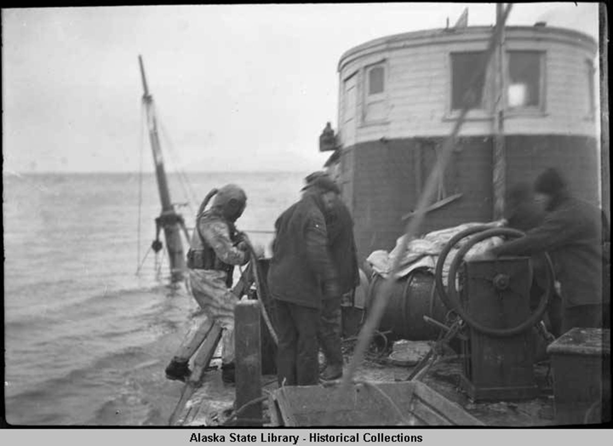 Diver and workers on boat above sunken Princess Sophia, 1918. (Alaska State Library Historical Collection, ASL-P87-1710)