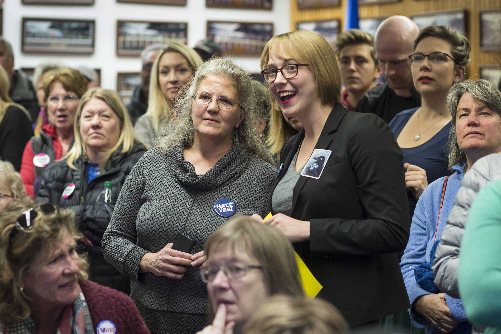 Assembly District 2 candidate Michelle Bonnet Hale, left center, and Assembly Areawide candidate Carole Triem watch their numbers soar as they watch Election results come in at the Assembly chambers on Tuesday, Oct. 2, 2018. (Michael Penn | Juneau Empire)