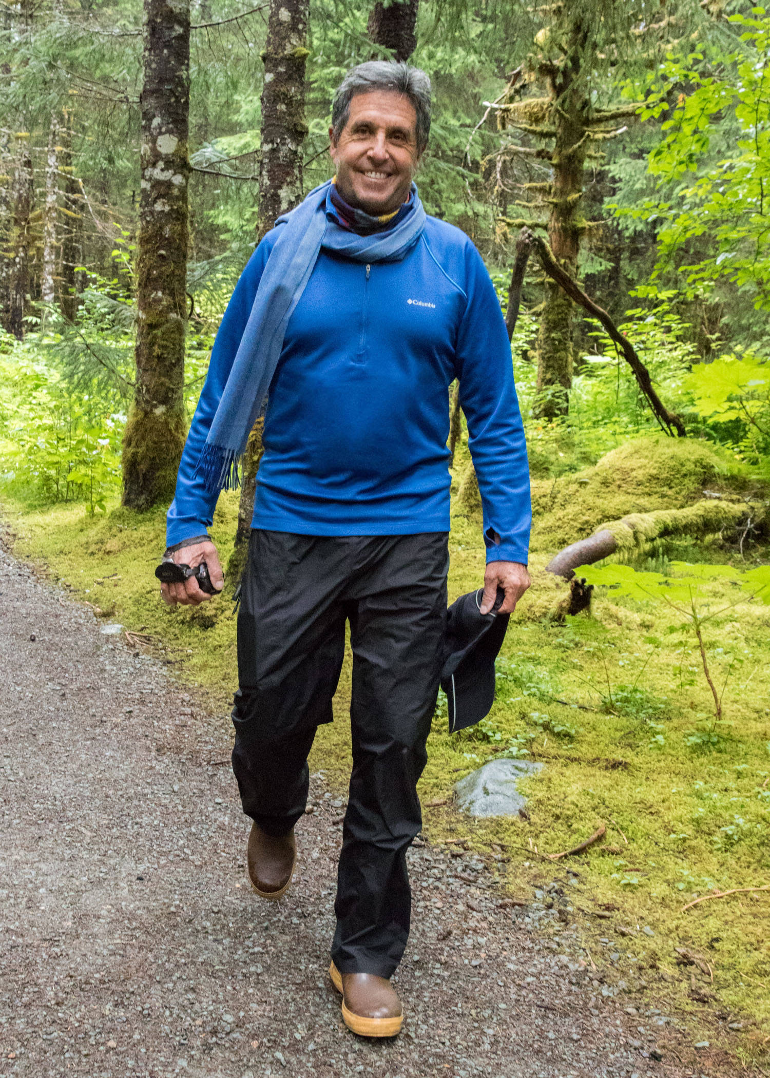 Oct. 21, 2018 Dirk Younkerman loves Alaska and has regularly visited and seasonally worked here since 1993. I ran into him on the trail on a rainy day where he was out enjoying the temperate rainforest. His practical clothes also looked smart—a royal blue Columbia fleece shirt, Kathmandu rain pants from New Zealand, Xtratufs, merino wool neck scarf and buff. An avid videographer, his most important accessories are his video camera and his ever-present smile, which reveals how much he enjoys Juneau.
