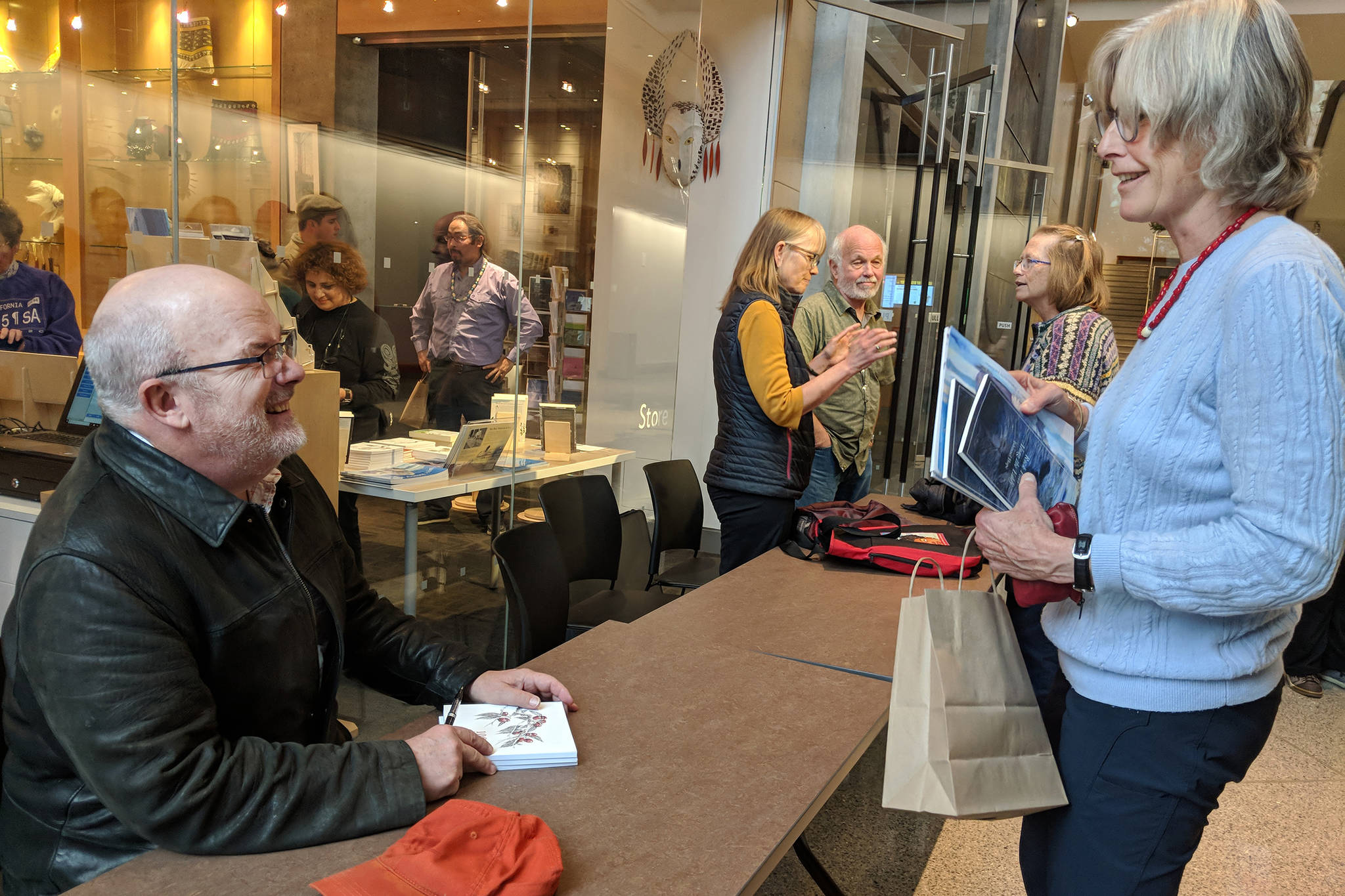 Author John Straley prepares to sign a book for author Heather Lende after the Alaska Literary Festival at the Father Andrew P. Kashevaroff building. They were both speakers at the event. (Ben Hohenstatt | Capital City Weekly)