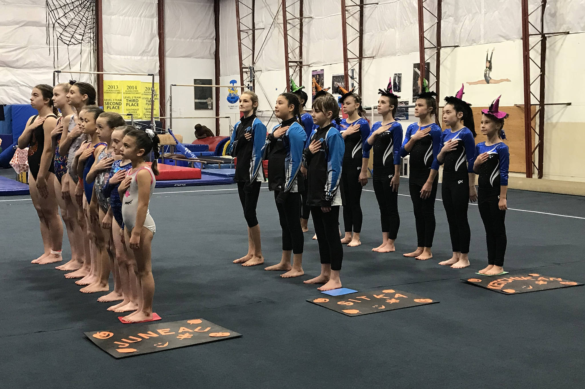 "Southeast teams from Juneau, left, Sitka, center, and Ketchikan, right, stand for the national anthem at the start of the ""Halloween Classic"" gymnastics meet on Saturday morning at the Southeast Alaska Gymnastics Academy in the Mendenhall Valley. The USA Gymnastics-sanctioned meet included 50 gymnasts competing on all four girls' events: vault, uneven bars, balance beam and floor exercise, and in the all around. Juneau's Kristie Kulbeth, Skylar Oliva and Megan Lujan ranked first in their respective age classes and divisions. (Courtesy Photo 