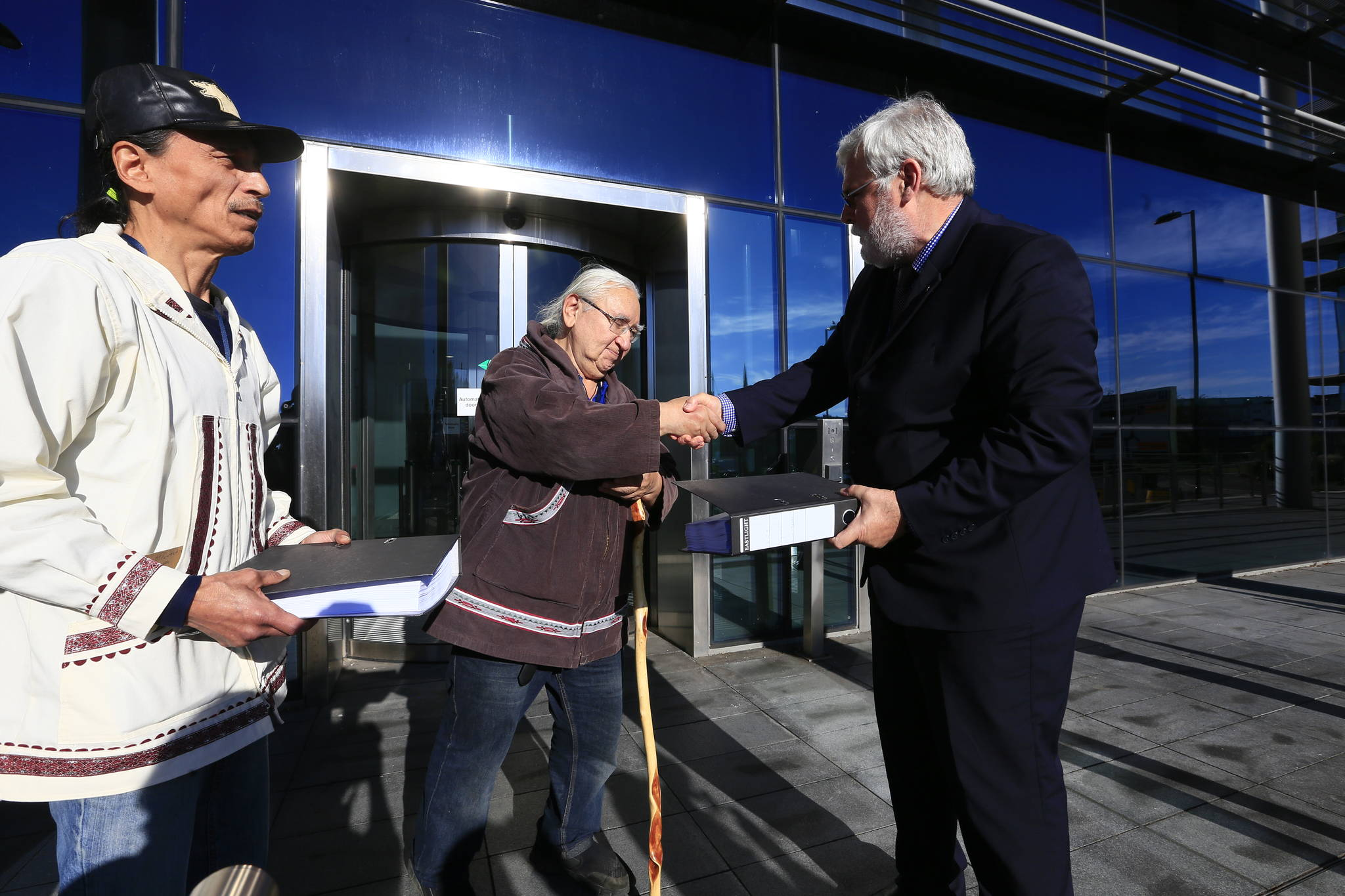 George Edwardson, board member for Inuit Circumpolar Council-Alaska and President of the Inupiat Community of the Arctic Slope (ICAS) hands the first of three binders holding over 104,000 signatures on an international petition calling for Carnival Corporation to end its use of heavy fuel oil in the Arctic and Subarctic to Tom Strang, Senior Vice President of Maritime Affairs for cruise industry giant. In July this year, the Inuit Circumpolar Council issued a formal Declaration calling for a phaseout of heavy fuel oil in the region. (Courtesy Photo | Jiri Rezac via Stand.earth)