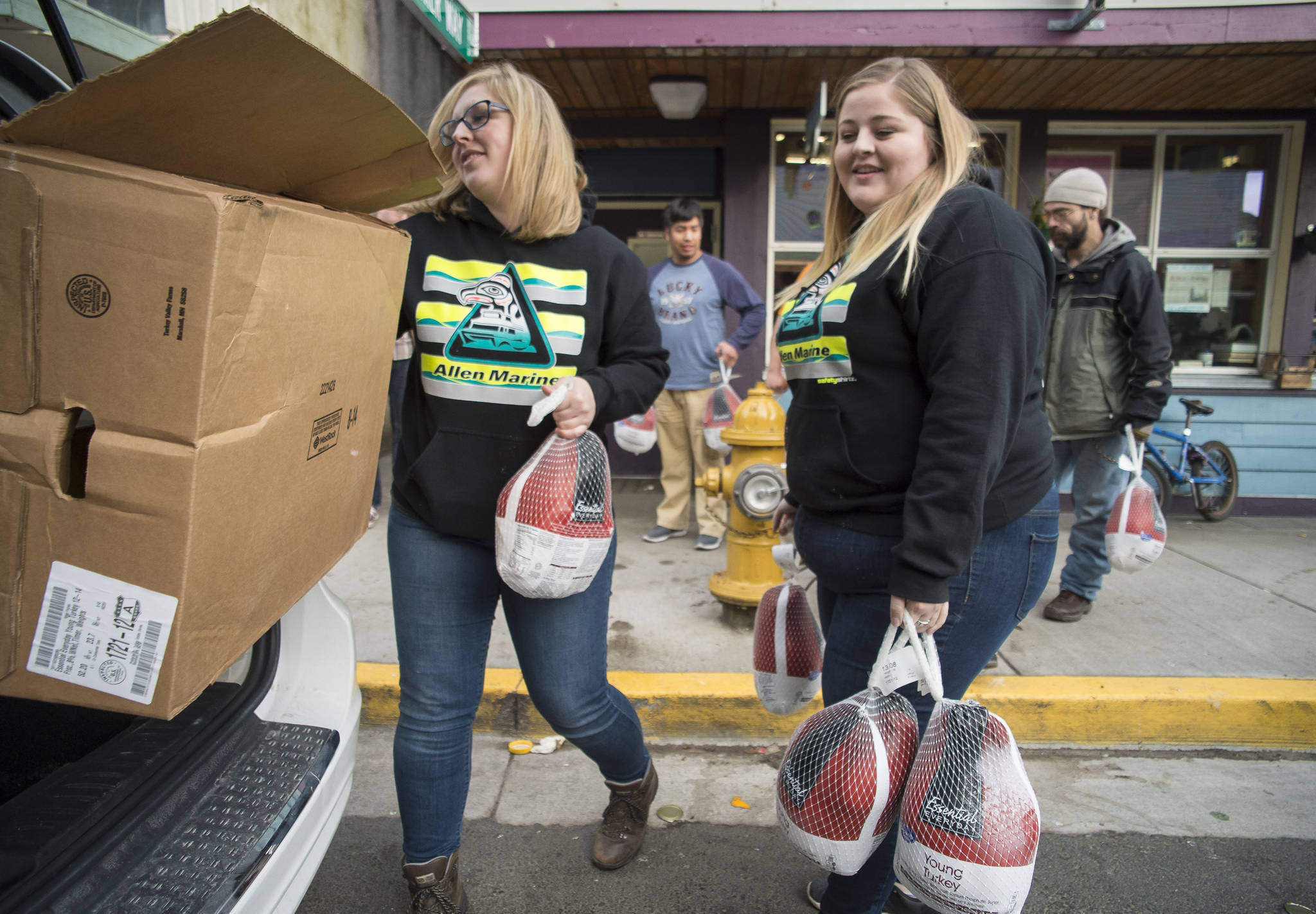 Cassandra Strahin, left, and Nicole Huntsman, of Allen Marine, deliver 30 frozen turkeys to the Glory Hole on Monday, Nov. 6, 2017. (Michael Penn | Juneau Empire File)