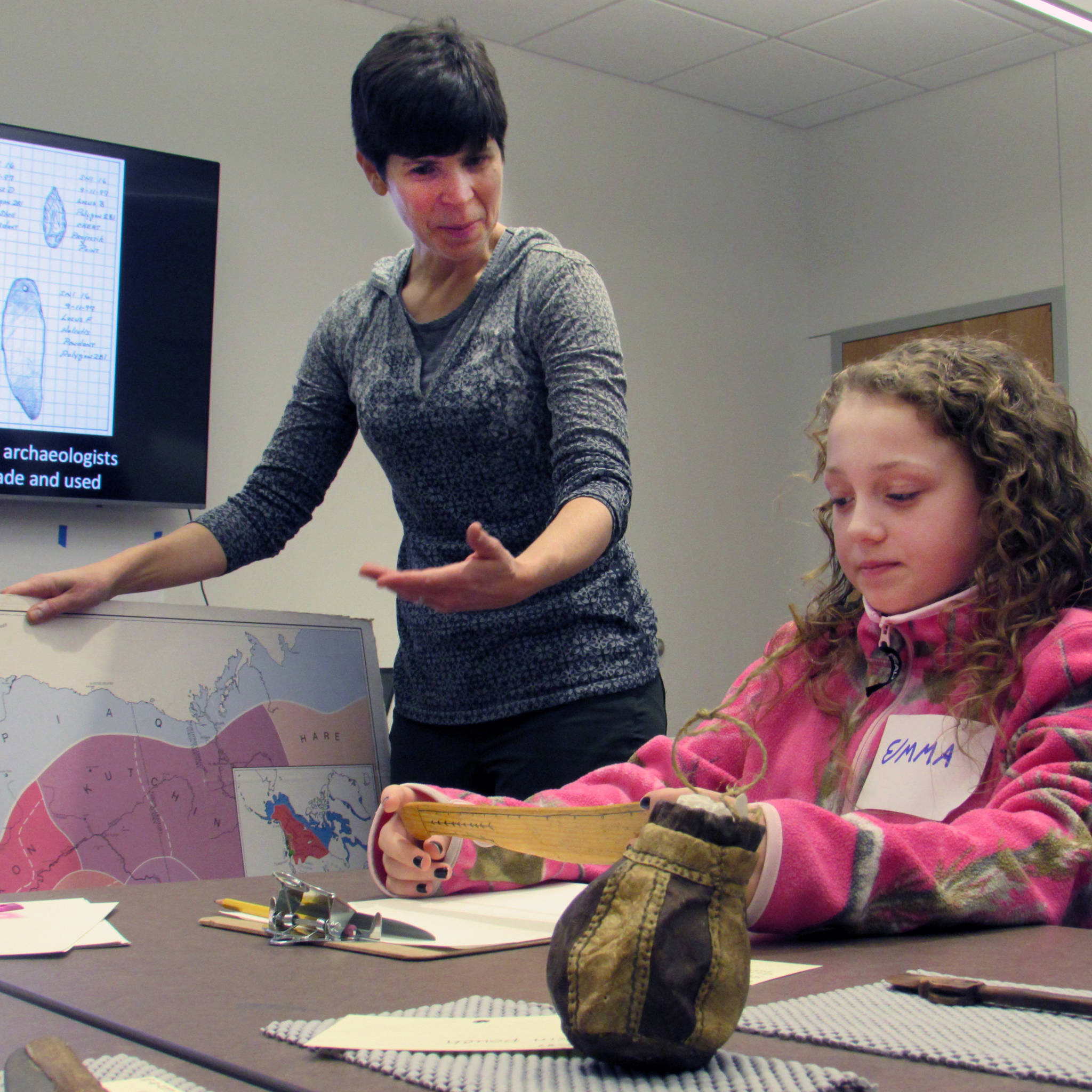 Science illustrator Kathy Hocker talks to Emma Dorsey, 10, who contemplates an artifact that she might sketch. (Ben Hohenstatt Capital City Weekly)