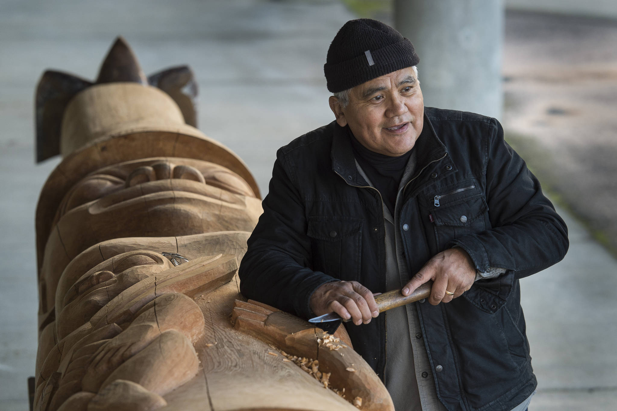 Wayne Price, master Tlingit carver and Associate Professor of Northwest Coast Arts and Sciences, works on a healing pole at the University of Alaska Southeast on Wednesday, Oct. 31, 2018. (Michael Penn   Juneau Empire)