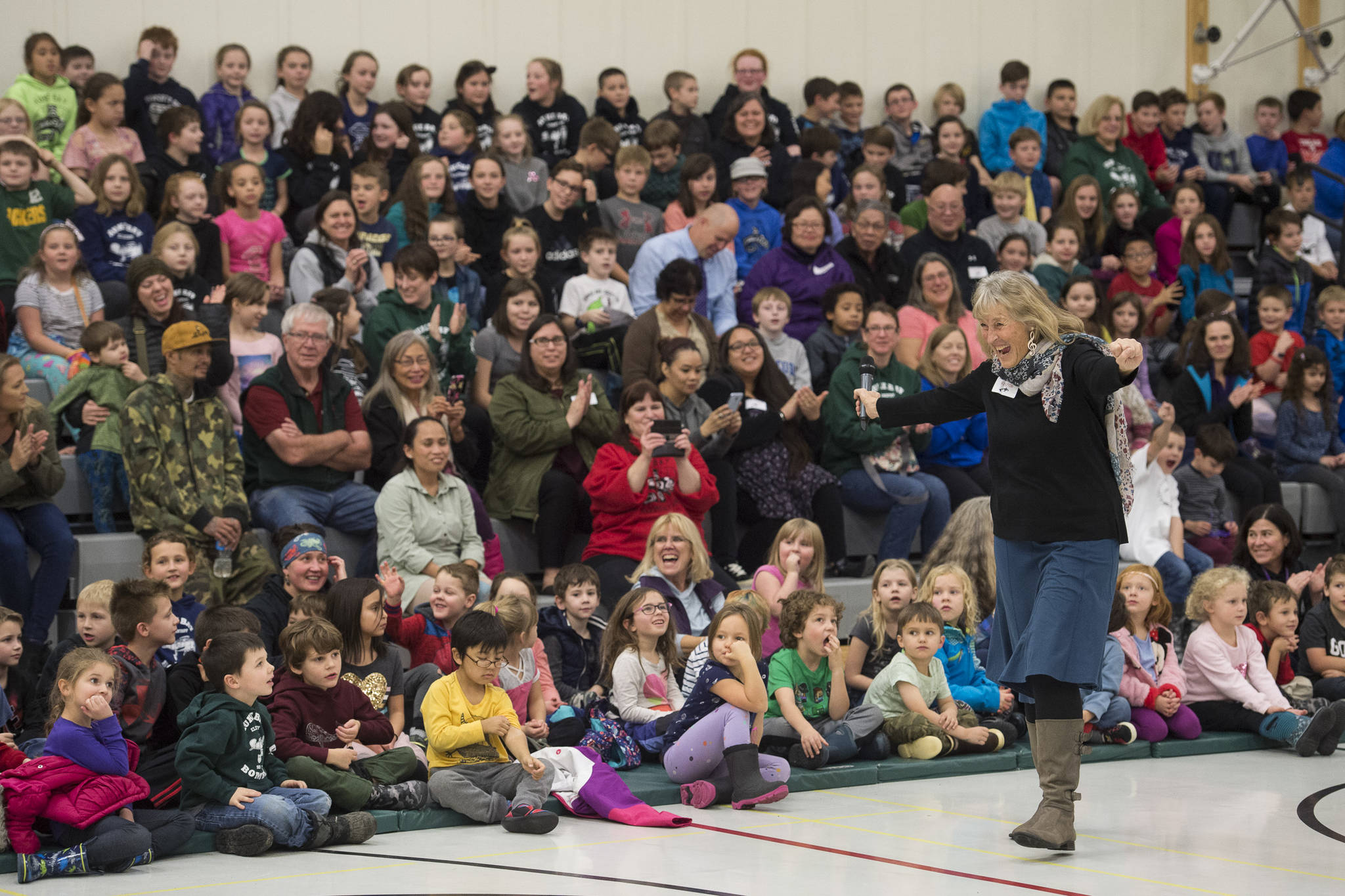Former teacher Linda Buckley leads Auke Bay Elementary School students in the school song on Friday, Nov. 9, 2018. (Michael Penn | Juneau Empire)