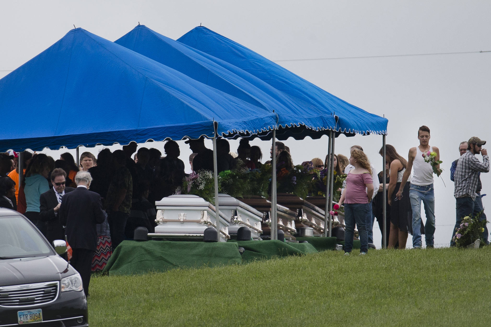 In this May 3, 2016 photo, mourners gather around caskets for six of the eight members of the Rhoden family found shot April 22, 2016, at four properties near Piketon, Ohio, during funeral services at Scioto Burial Park in McDermott, Ohio. Authorities said Tuesday, Nov. 13, 2018, that a family of four has been arrested in in the slayings of eight members of one family in rural Ohio two years ago. (John Minchillo | Associated Press File)