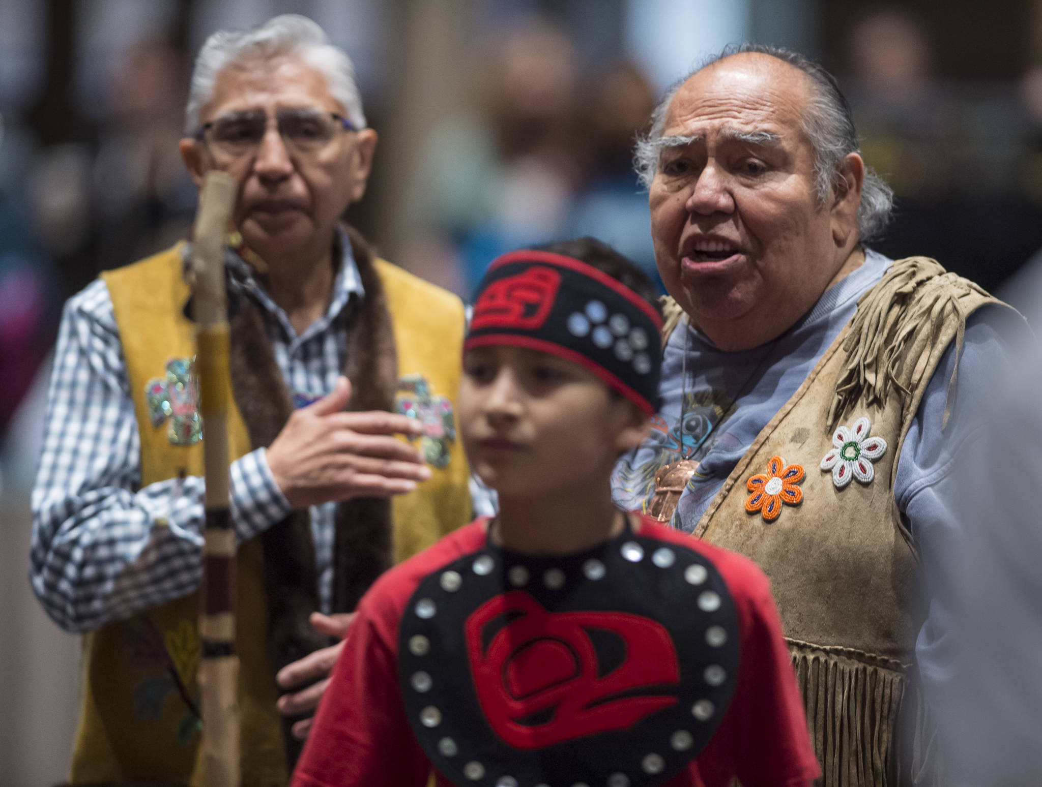 Tlingit elders David Katzeek, right, and Paul Marks, left, watch as Tyler Frisby, a member of the Tlingit Culture Language and Literacy Dance Group from Harborview Elementary School dance exits during the Voices of Our Ancestors Language Summit at Centennial Hall on Tuesday, Nov. 13, 2018. (Michael Penn | Juneau Empire)