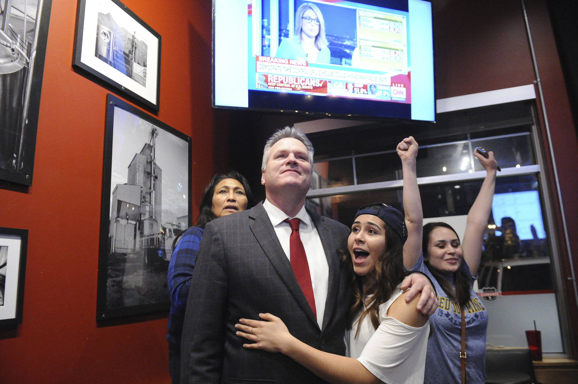 Republican gubernatorial candidate Mike Dunleavy reacts to early favorable election returns on Nov. 6, 2018 in Anchorage. With Dunleavy are from left, his wife Rose and daughters Ceil and Maggie. (Michael Dinneen | Associated Press)