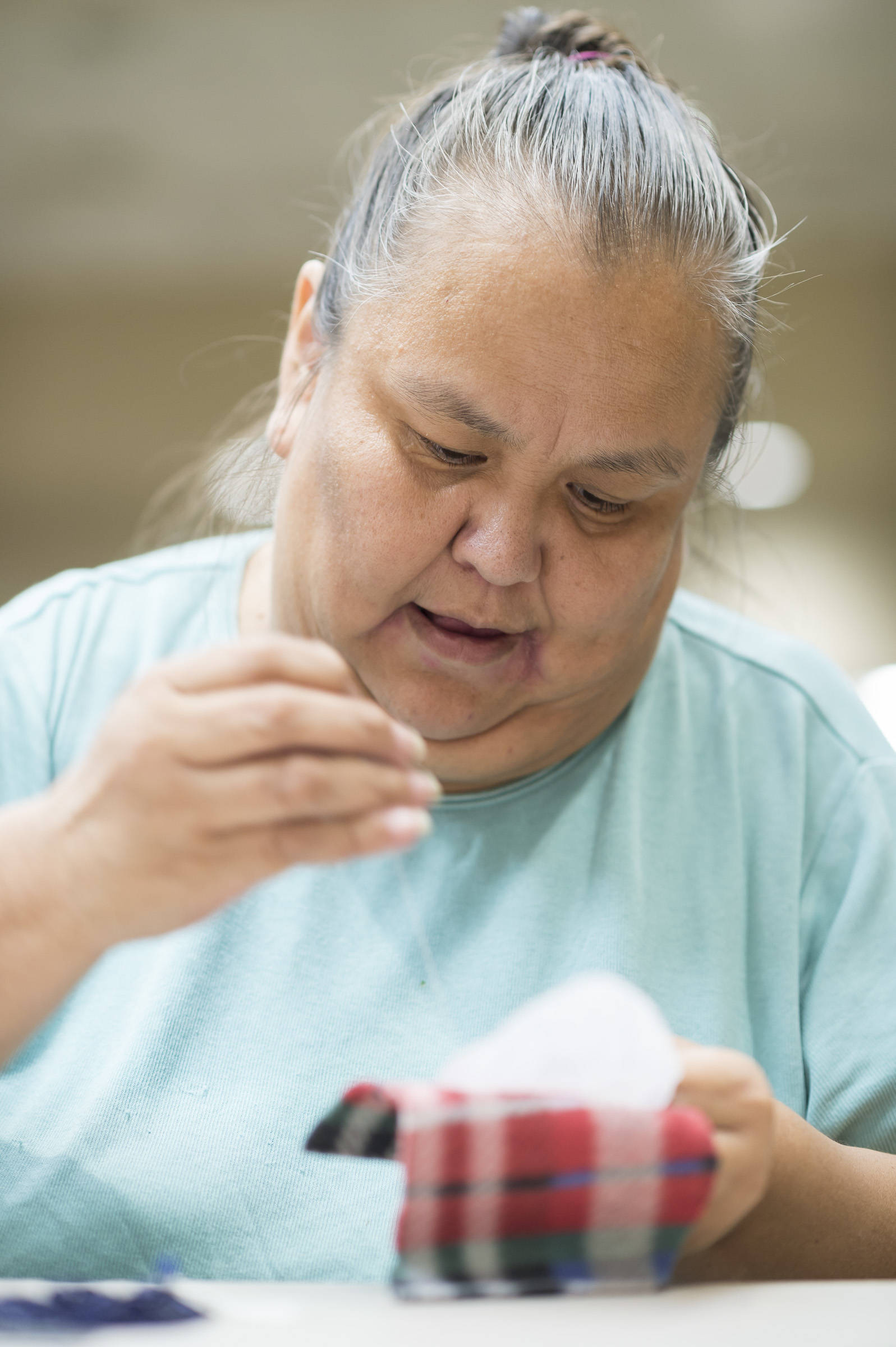 Cecelia Friberg-Rodriguez works on beading a pendant during the Celebrating Our Ways of Life for Native American Heritage Month at the Elizabeth Peratrovich Hall on Friday, Nov. 16, 2018. (Michael Penn   Juneau Empire)