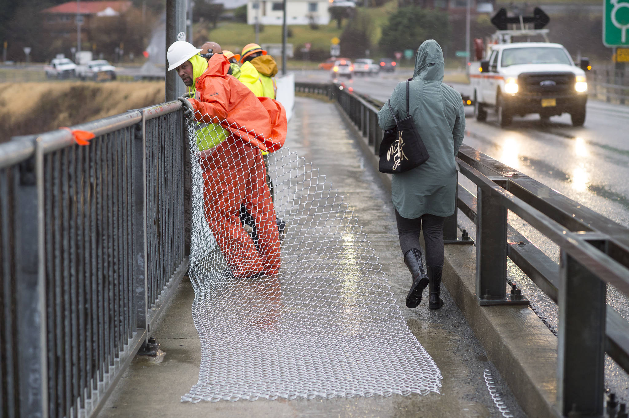A crew from the Department of Transportation and Public Facilities installs chain-link fencing along the pedestrian walkway over the Douglas Bridge on Monday, Nov. 26, 2018. (Michael Penn | Juneau Empire)