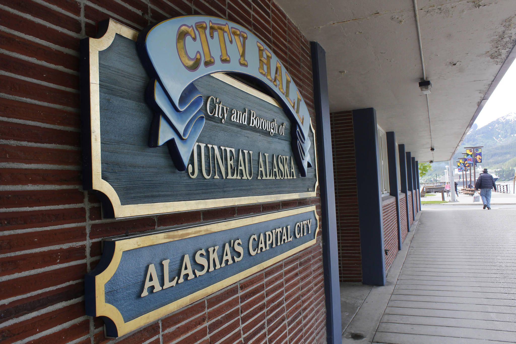 A pedestrian walks by City Hall on June 7, 2017. (Alex McCarthy | Juneau Empire File)