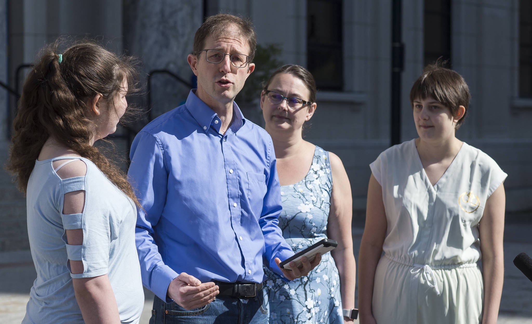 Jesse Kiehl announces his run for Senate District Q in front of the Alaska State Capitol with his wife, Karen Allen, and their daughters, Adara Allen, 13, left, and Tsifira Kiehl, 16, right, on Thursday, May 17, 2018. (Michael Penn | Juneau Empire)