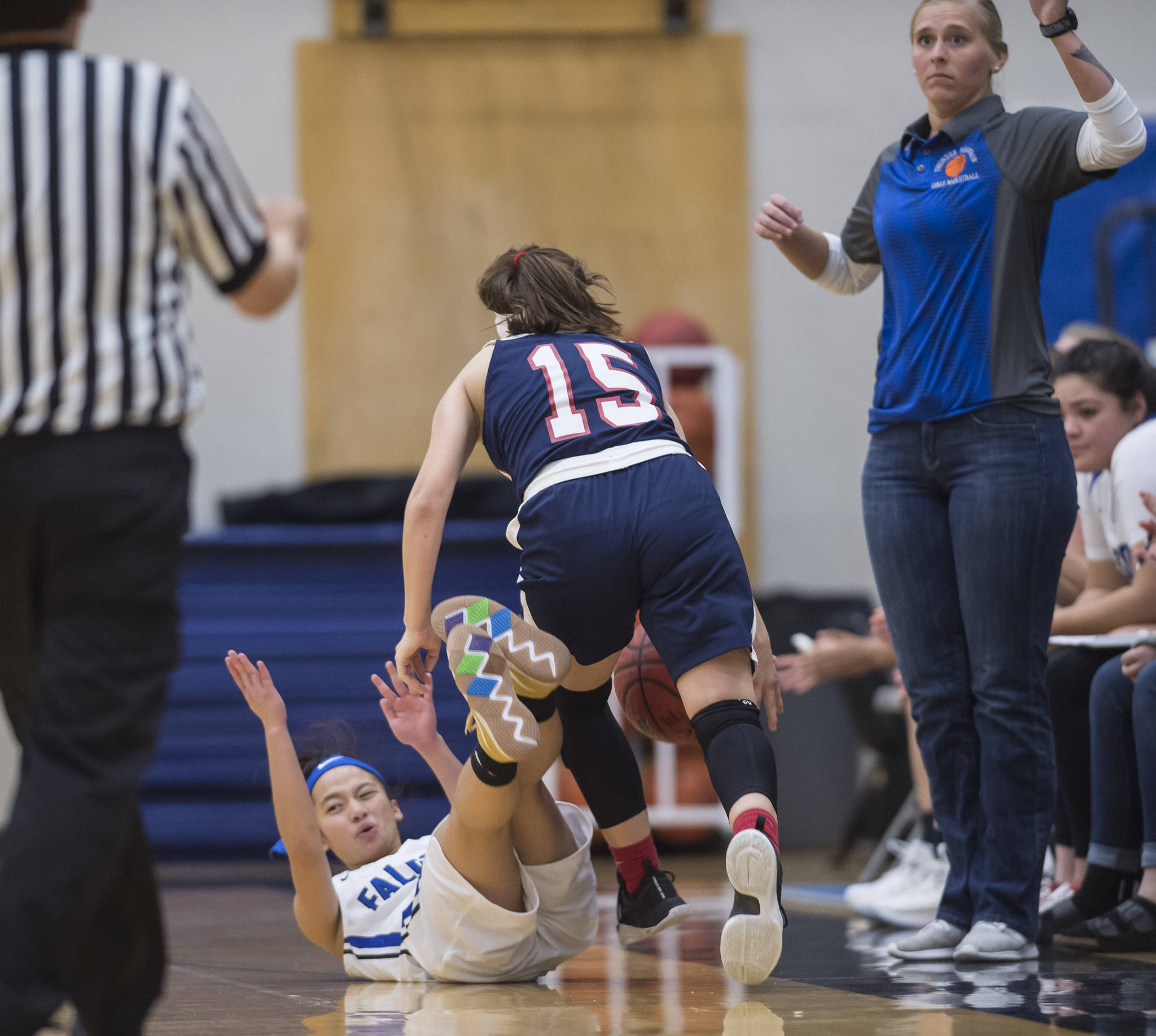 Thunder Mountain's Mary Neal Garcia falls and is called for a foul against North Pole's Laura Donovan at TMHS on Thursday, Dec. 13, 2018. (Michael Penn | Juneau Empire)
