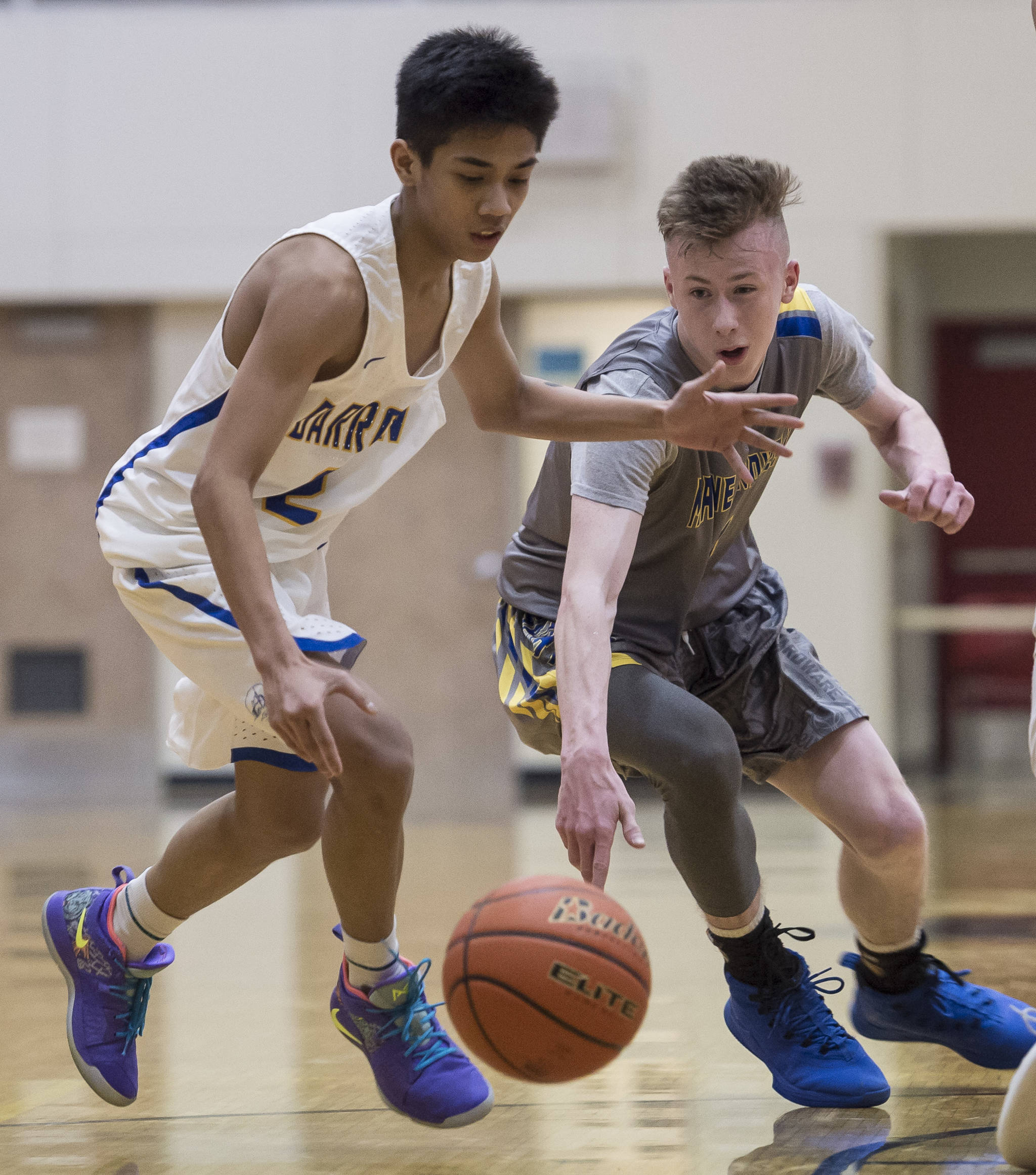 Barrow's Karl Nobleza, left, and Maine-Endwell's Jack Coleman battle for a loose ball at the Princess Cruises Capital City Classic at Juneau-Douglas High School on Thursday, Dec. 27, 2018. Barrow won 73-69. (Michael Penn | Juneau Empire)